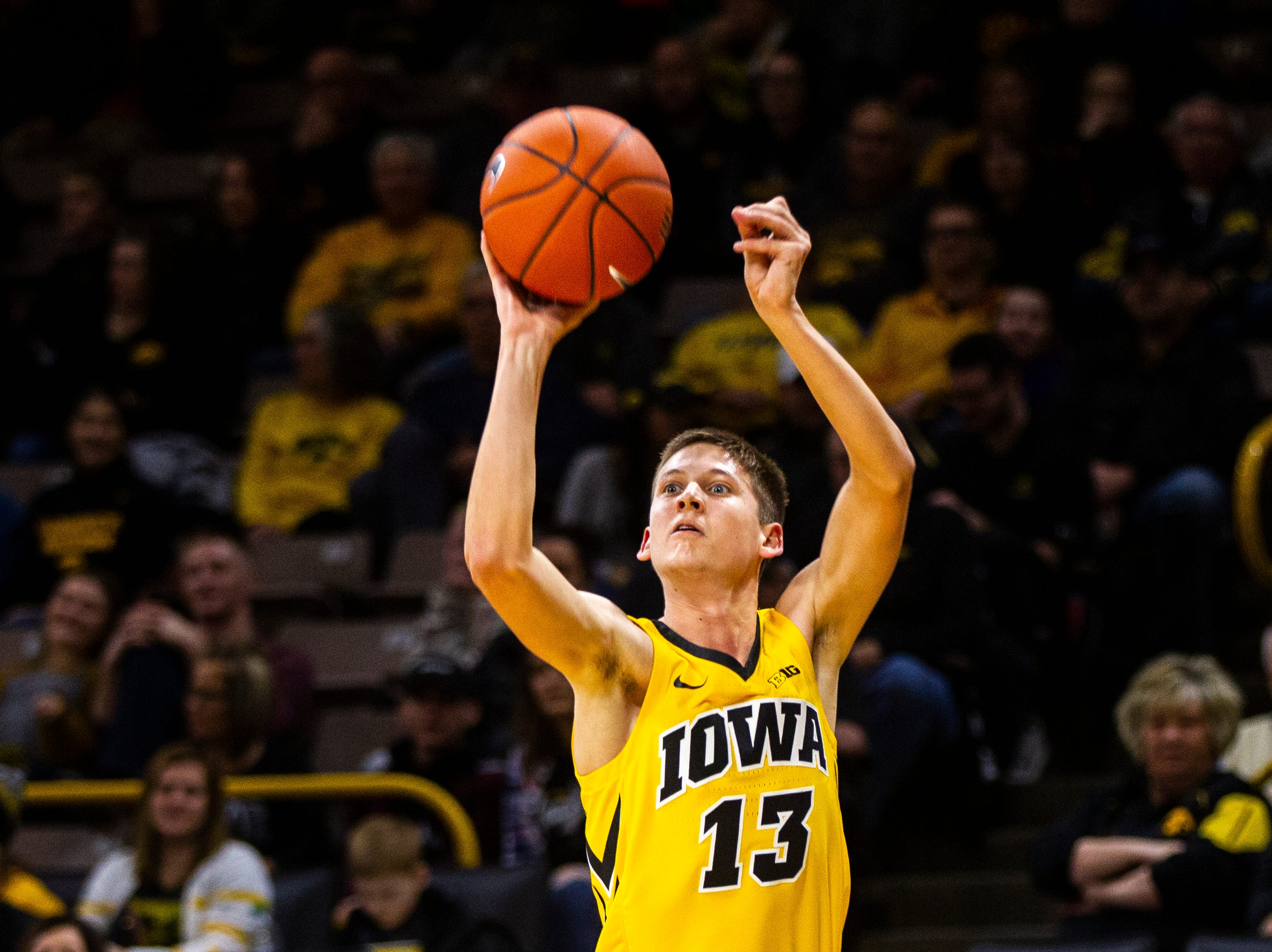 Iowa guard Austin Ash (13) shoots a 3-point basket during a NCAA men's basketball game on Saturday, Dec. 22, 2018, at Carver-Hawkeye Arena in Iowa City.