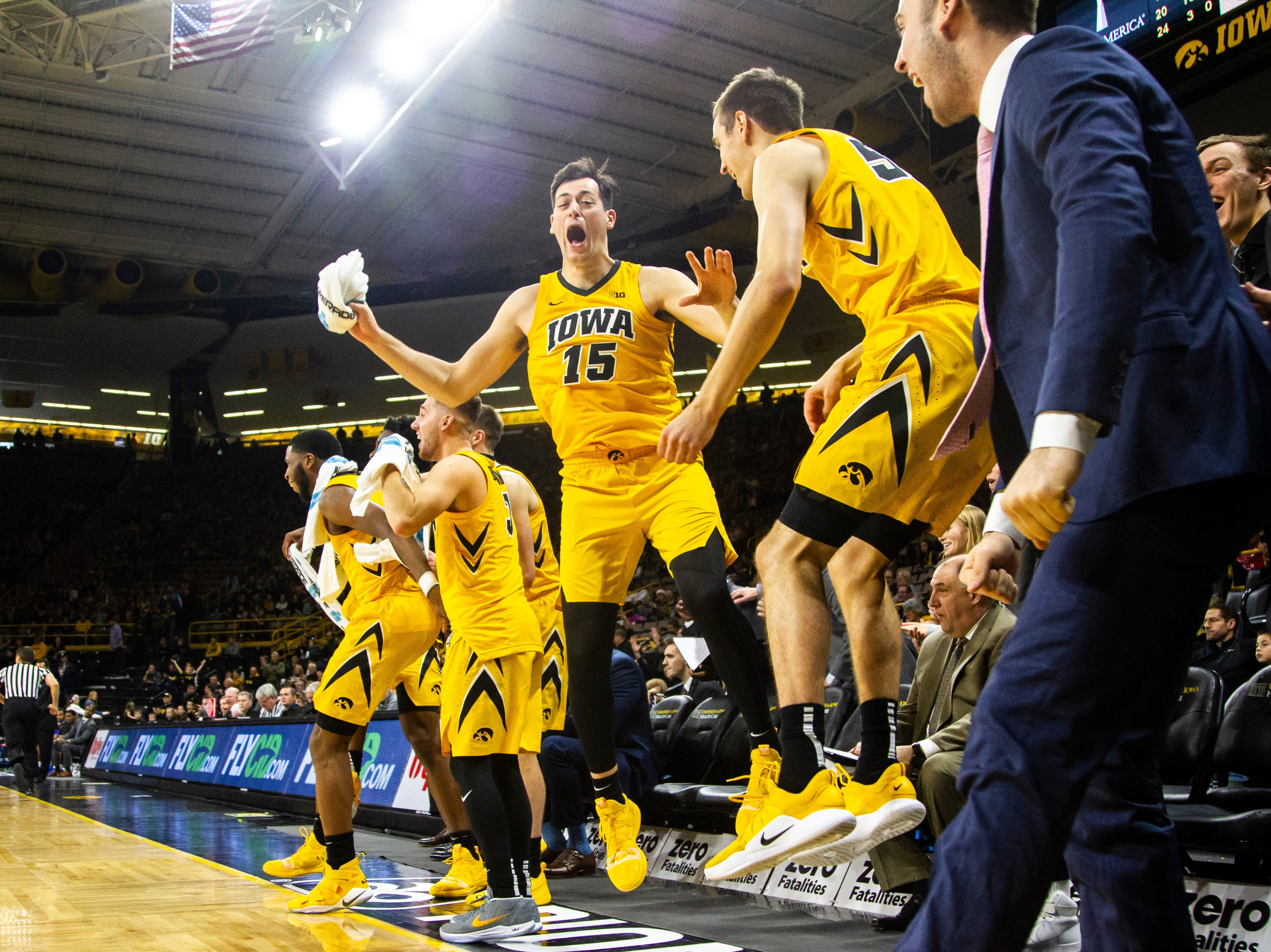 Iowa forward Ryan Kriener (15) leaps in the air with Iowa forward Nicholas Baer (51) while they celebrate a teammate's basket during a NCAA men's basketball game on Saturday, Dec. 22, 2018, at Carver-Hawkeye Arena in Iowa City.