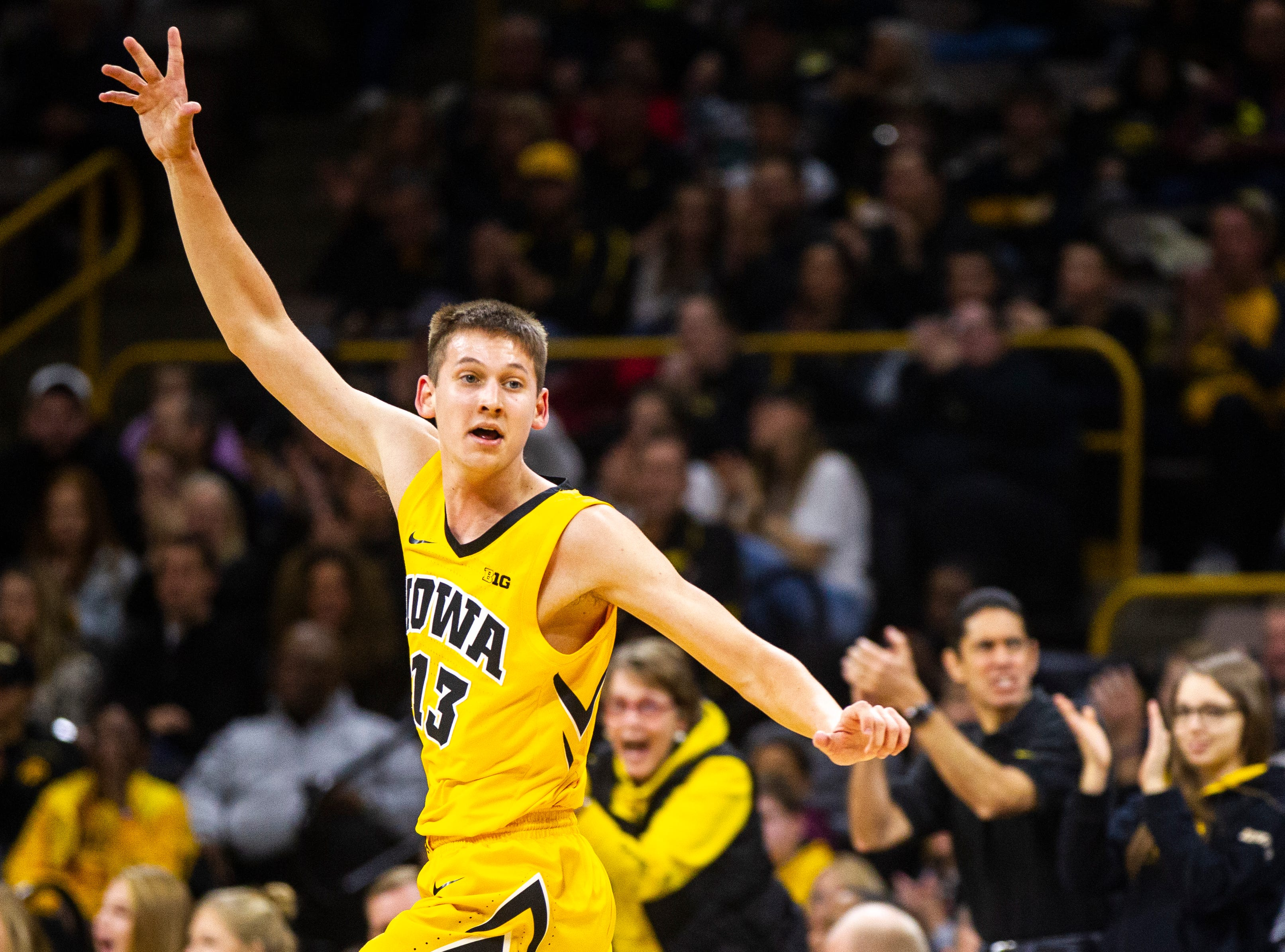 Iowa guard Austin Ash (13) celebrates after making a 3-point basket during a NCAA men's basketball game on Saturday, Dec. 22, 2018, at Carver-Hawkeye Arena in Iowa City.