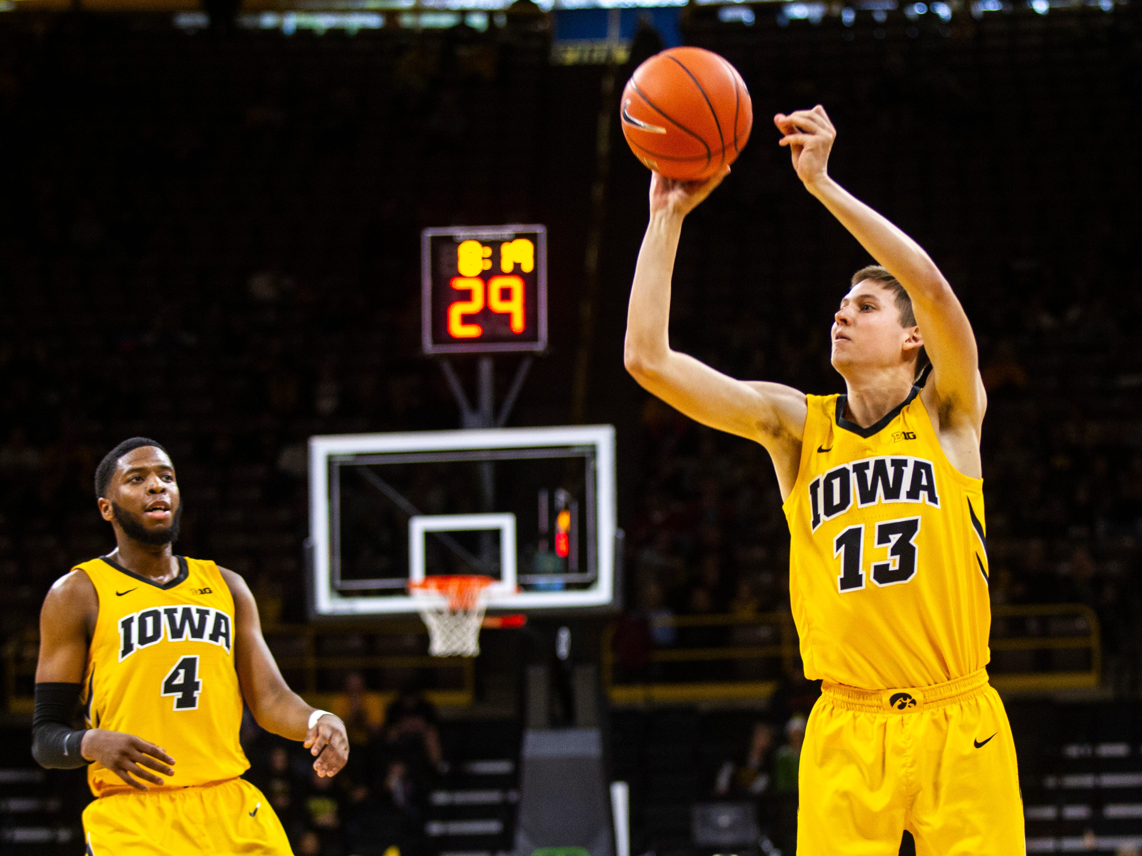 Iowa guard Austin Ash (13) shoots a 3-point basket as Iowa guard Isaiah Moss (4) looks on during a NCAA men's basketball game on Saturday, Dec. 22, 2018, at Carver-Hawkeye Arena in Iowa City.