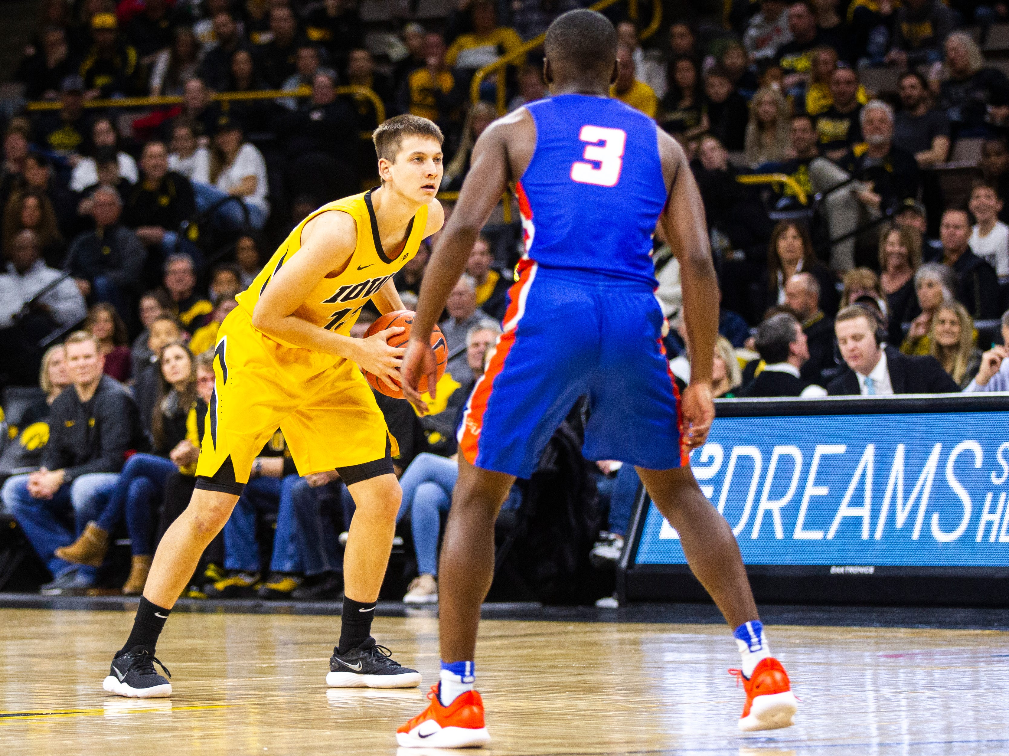 Iowa guard Austin Ash (13) looks to pass during a NCAA men's basketball game on Saturday, Dec. 22, 2018, at Carver-Hawkeye Arena in Iowa City.