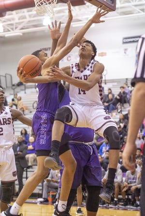 Lawrence Central High School junior Dre Davis (14) goes to the basket along the baseline during the first half of action. Lawrence Central High School hosted Ben Davis High School in IHSAA varsity basketball action, Friday, Dec. 21, 2018.