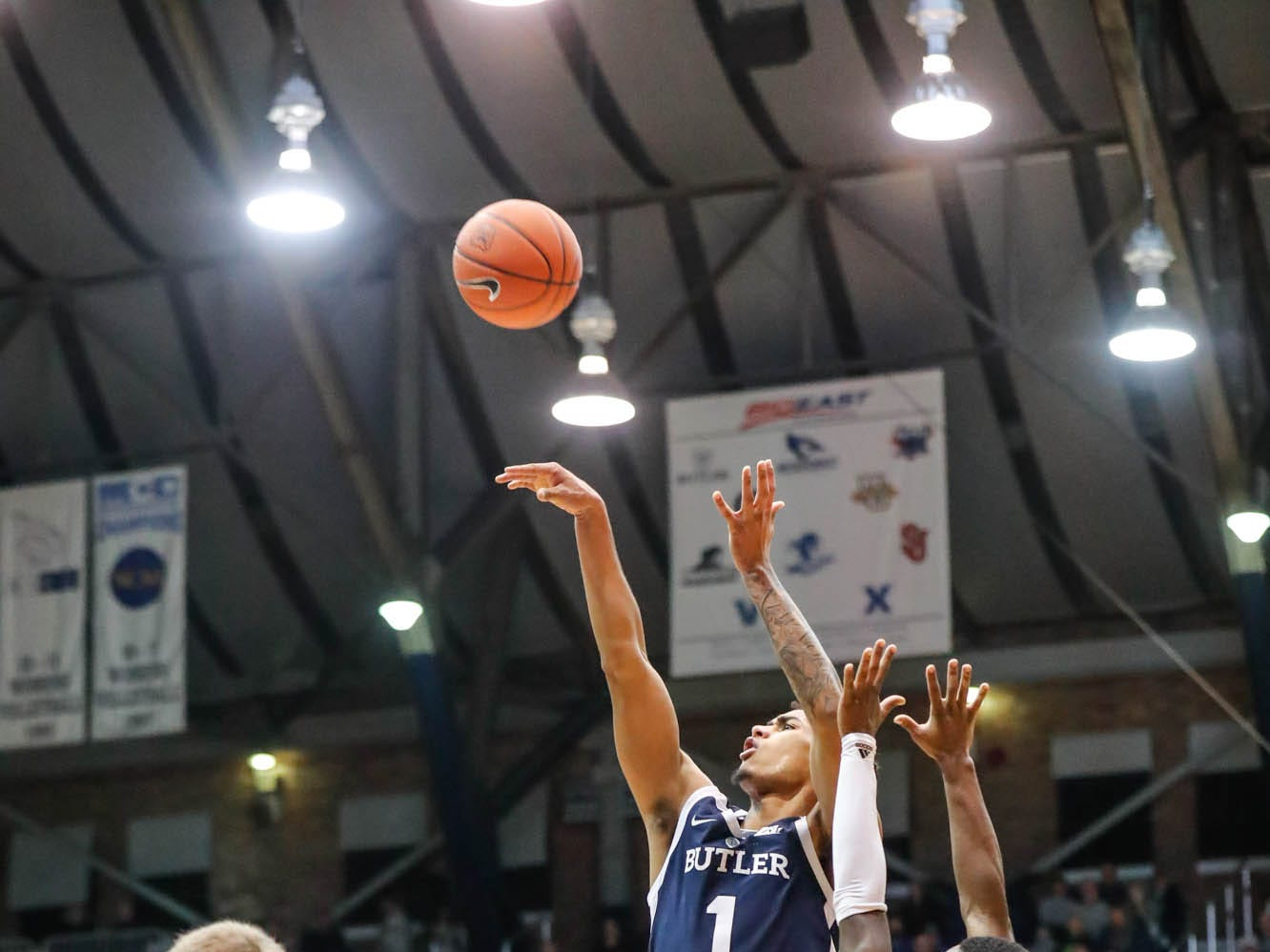 Butler University's forward Jordan Tucker (1) shoots over UC Irvine's guard Max Hazzard (2), and UC forward Tommy Rutherford (42), during a game between Butler University and UC Irvine, at Hinkle Fieldhouse on Friday, Dec. 21, 2018.