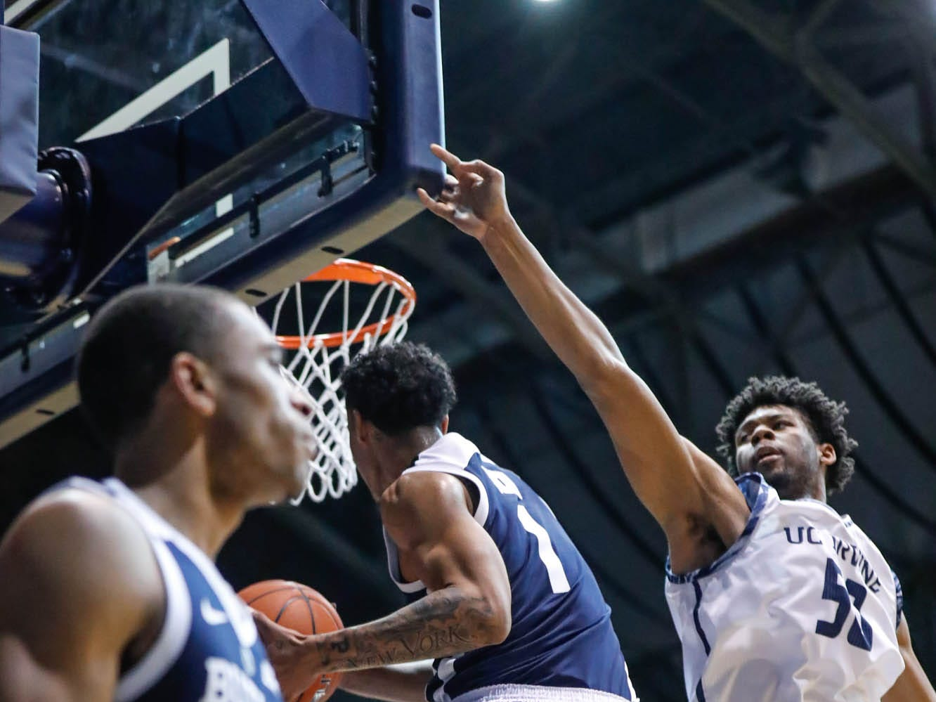 Butler University's forward Jordan Tucker (1) shoots a layup, but a foul is called, during a game between Butler University and UC Irvine, at Hinkle Fieldhouse on Friday, Dec. 21, 2018. Butler University's guard Aaron Thompson (2), UC Irvine's forward Elston Jones (50).
