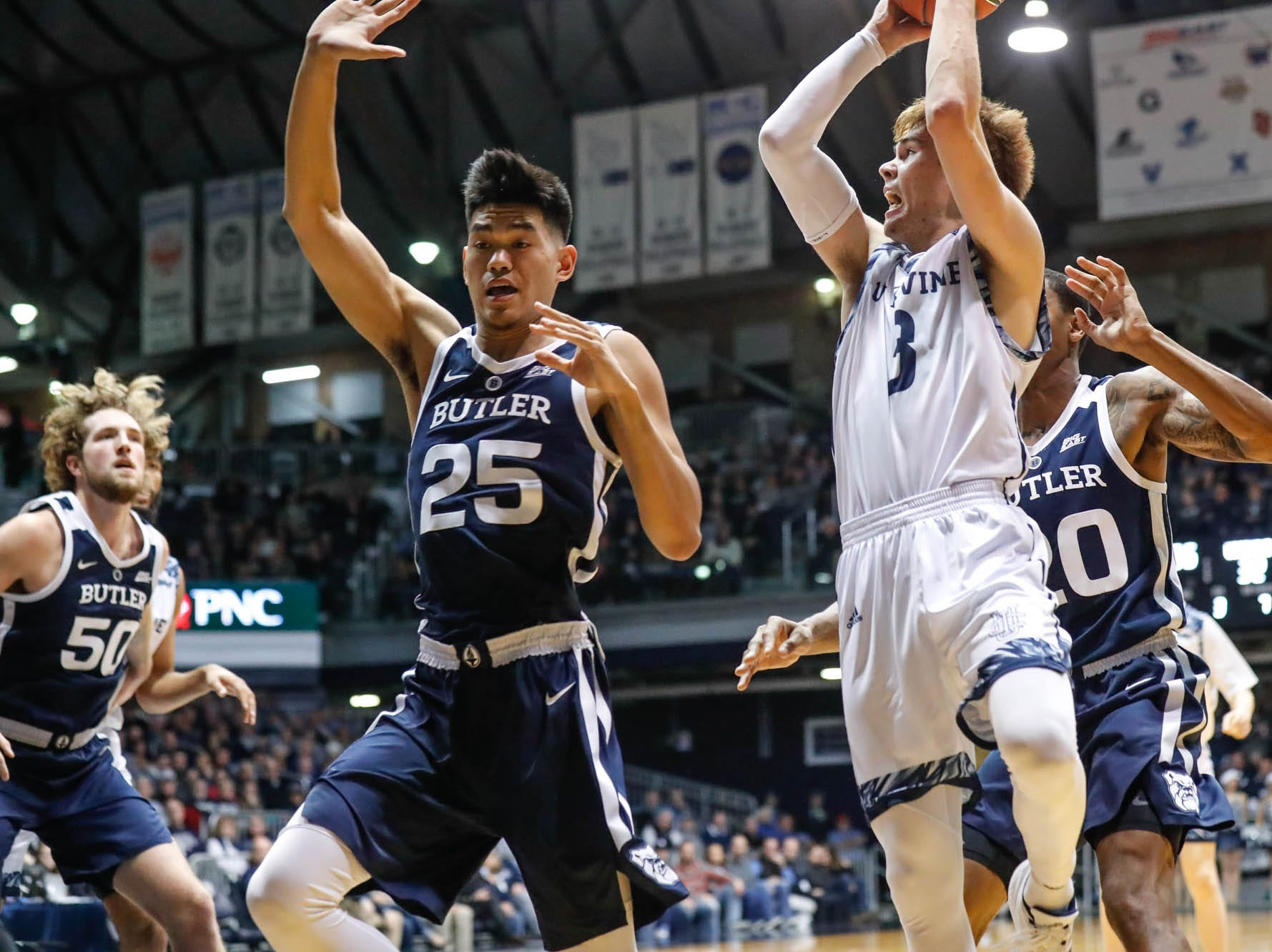 Butler University's forward Christian David (25), attempts to block a shot by UC Irvine's guard Robert Cartwright (3), during a game between Butler University and UC Irvine, at Hinkle Fieldhouse on Friday, Dec. 21, 2018. Butler University's center Joey Brunk (50), Butler University's guard/forward Henry Baddley (20).