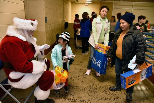 Santa Clause joined volunteers helping distribute Empty Stocking Fund baskets at Chilhowee Park on Saturday, December 22, 2018.