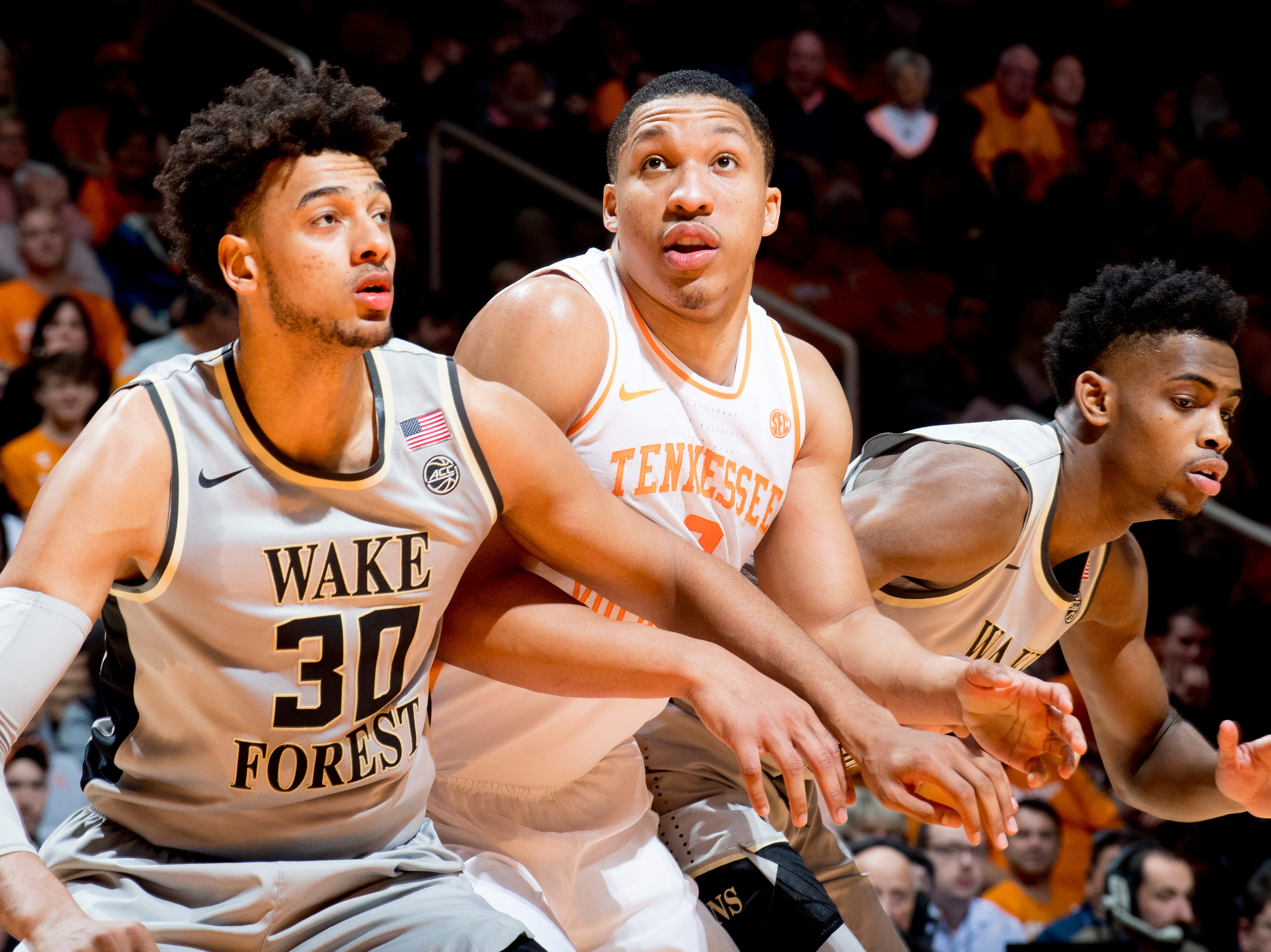 Wake Forest center Olivier Sara (30), Tennessee forward Grant Williams (2) and Wake Forest forward Jaylen Hoard (10) go for the rebound during a game between Tennessee and Wake Forest at Thompson-Boling Arena in Knoxville, Tennessee on Saturday, December 22, 2018.