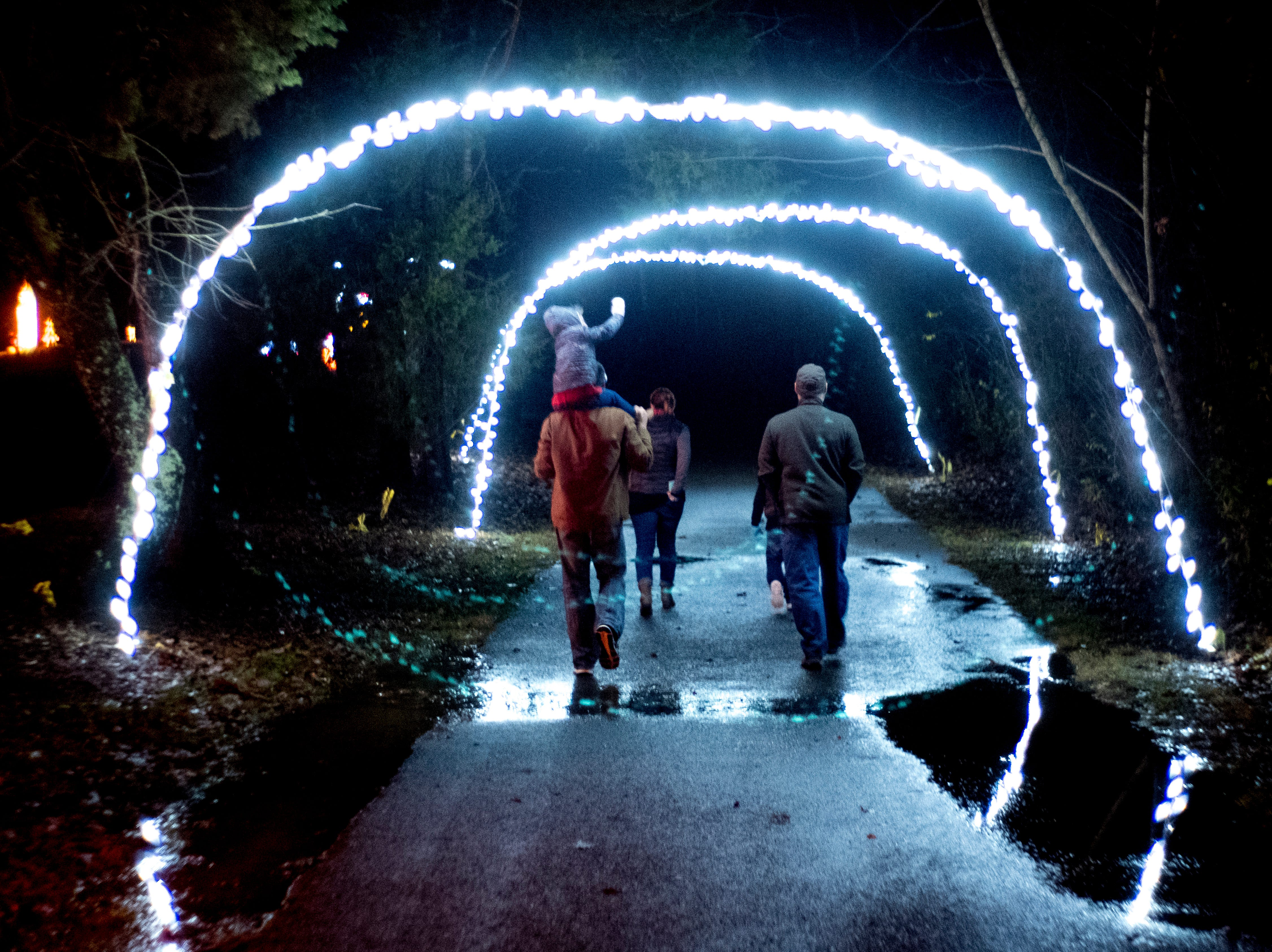 Visitors walk beneath an archway of lights at Knox CountyÕs 20th annual Holiday Festival of Lights kick off at The Cove at Concord Park in Farragut, Tennessee on Friday, December 21, 2018. The family-friendly event is free and will run through Dec. 29 from 6 to 9 p.m., excluding Christmas Eve and Christmas Day.