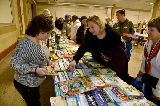 Volunteers  help distribute books and toys at the Empty Stocking Fund baskets at Chilhowee Park on Saturday, December 22, 2018.