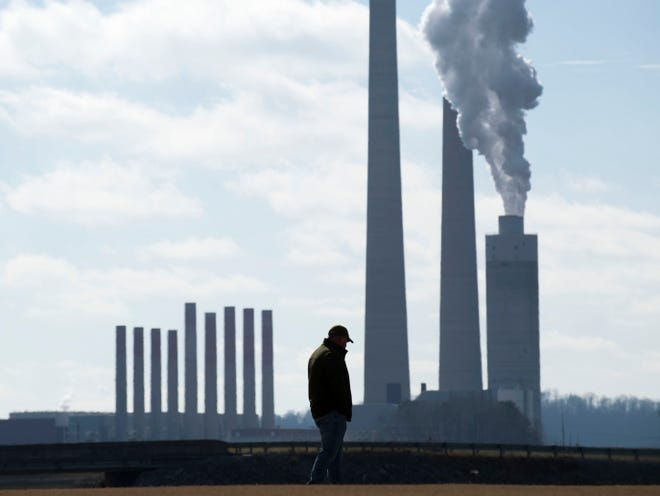 With the TVA Kingston Fossil Fuel Plant in the background, Brian Thacker stands at the Swan Pond Sports Complex on Saturday, the 10th anniversary of the plant's coal ash spill. Thacker operated a dredge and heavy machinery during the cleanup of the spill.