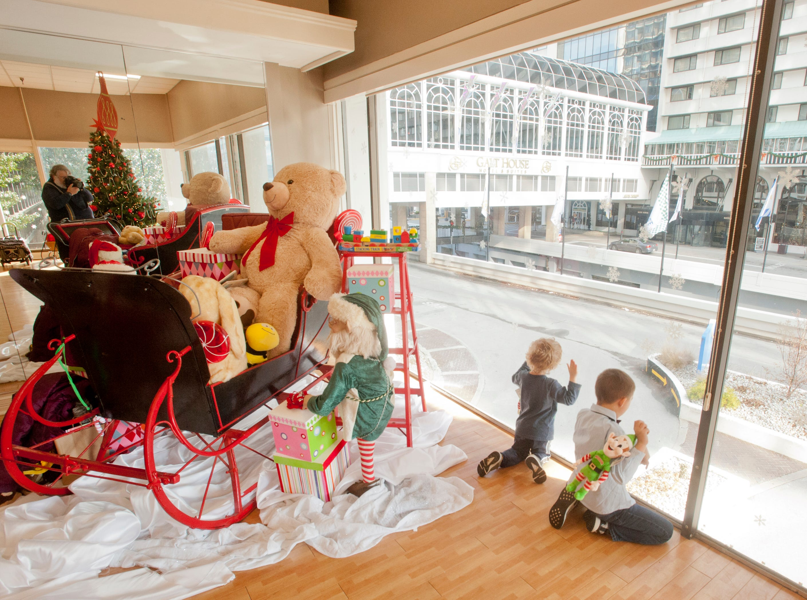 """Joshie Ferguson, age 4, left, and his cousin, Abram Williford, age 6, of Jeffersontown, peer out of the Galt House Hotel's glass window in St. Nick's room during the hotel's """"Breakfast with Santa"""" event.22 December 2018"""