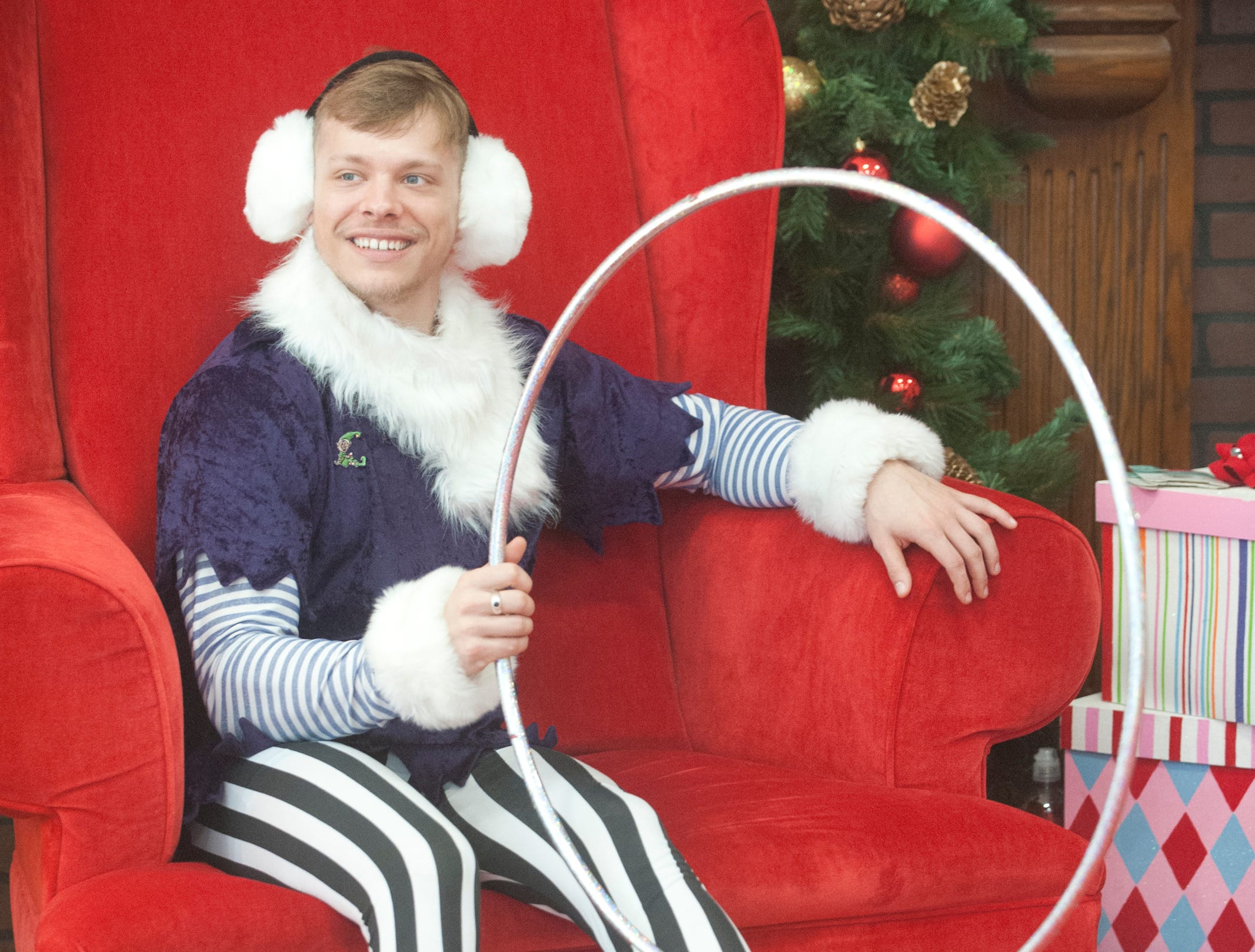 """CirqueLouis performer-elf Jordan Clark of Plantation sits in Santa's chair and plays with large hoop at the Galt House Hotel's sold-out event,  """"Breakfast with Santa.""""22 December 2018"""