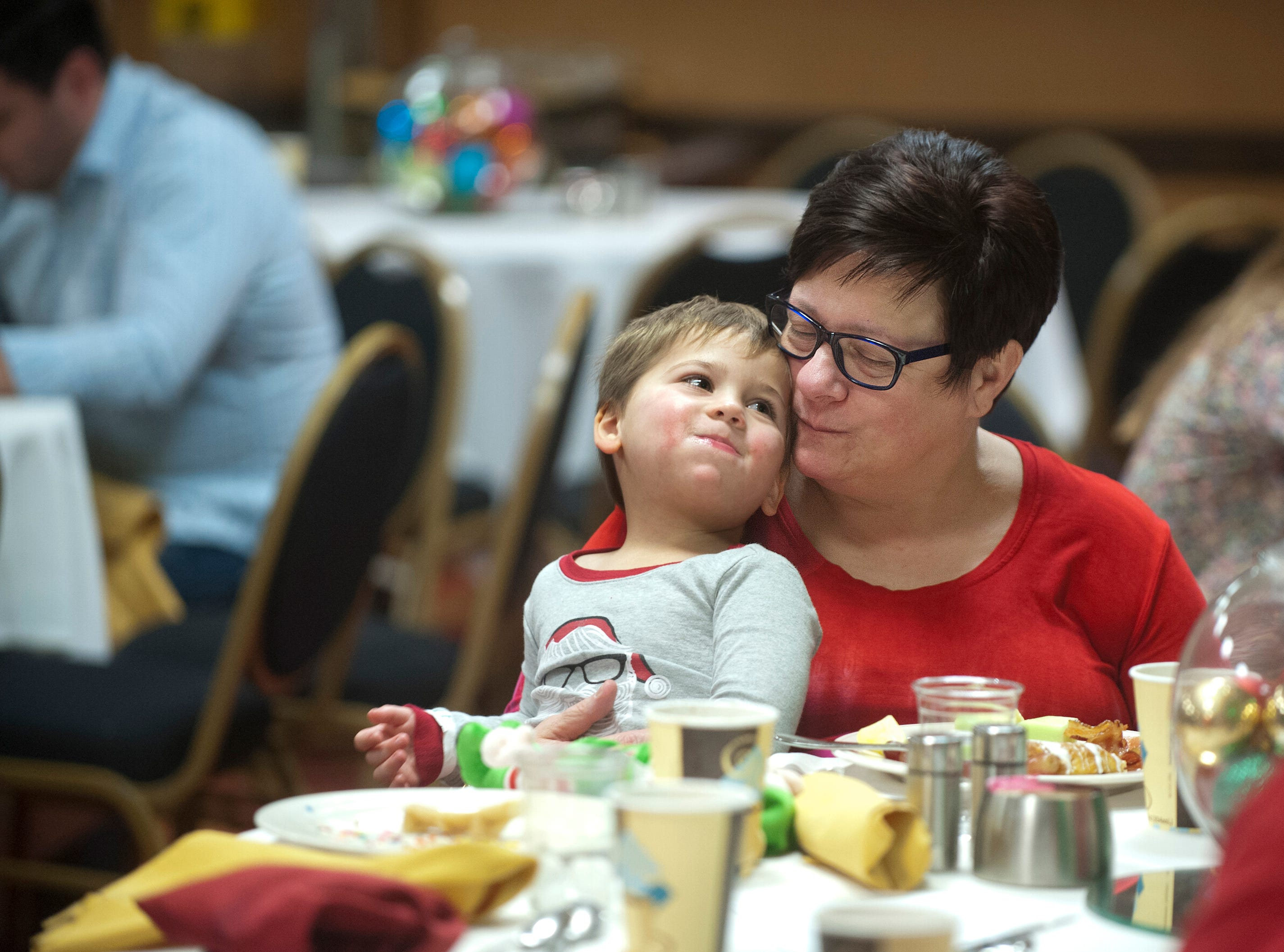 "Gunner Baker of Middletown snuzzles with her grandson, Gunner, of Shelbyville, at the Galt House Hotel's sold-out event,  ""Breakfast with Santa.""22 December 2018"