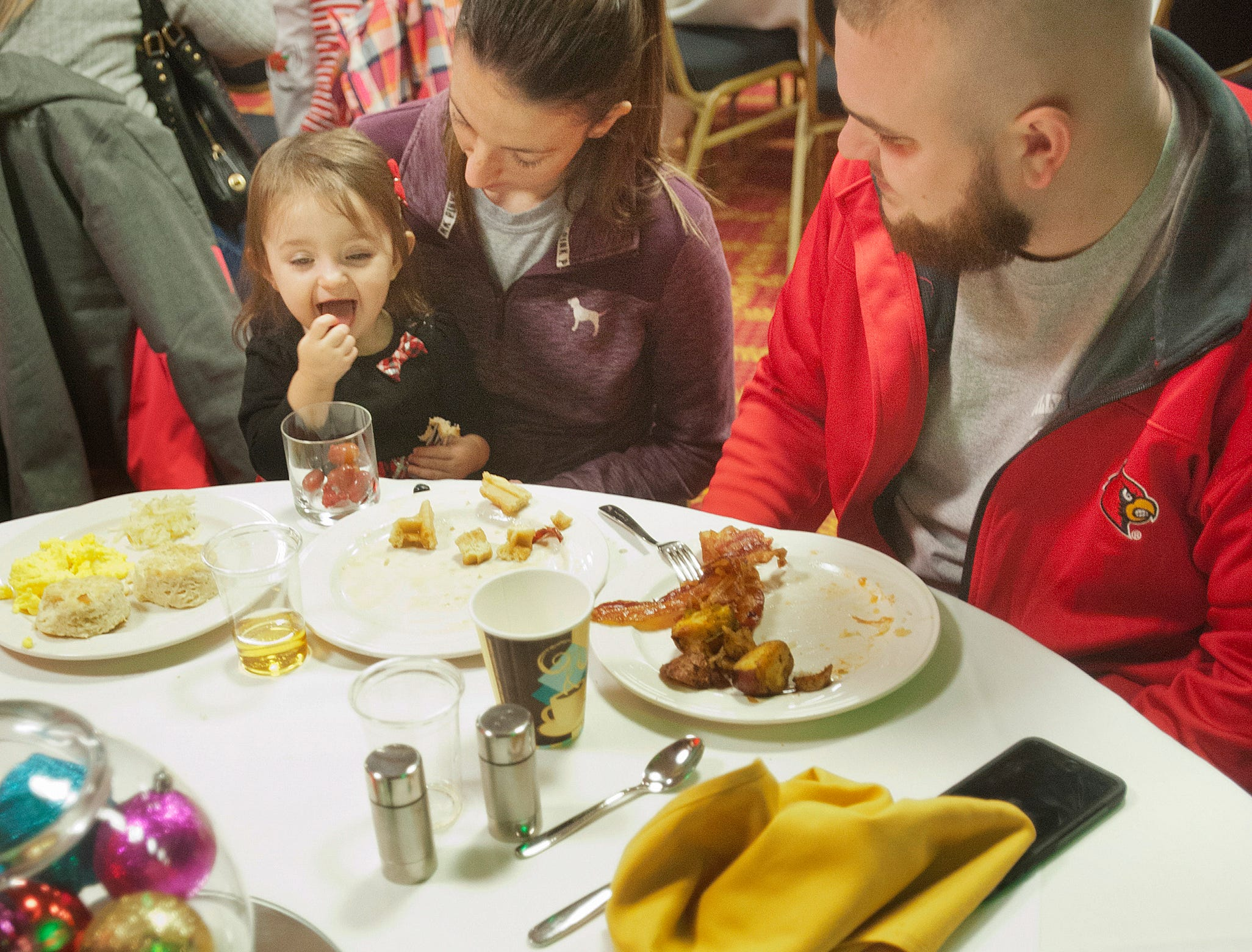 """Ashley and Sean Estep of Pleasure Ridge Park watch their daughter, Harper, age one, eat a candy at the Galt House Hotel's sold-out event,  """"Breakfast with Santa.""""22 December 2018"""