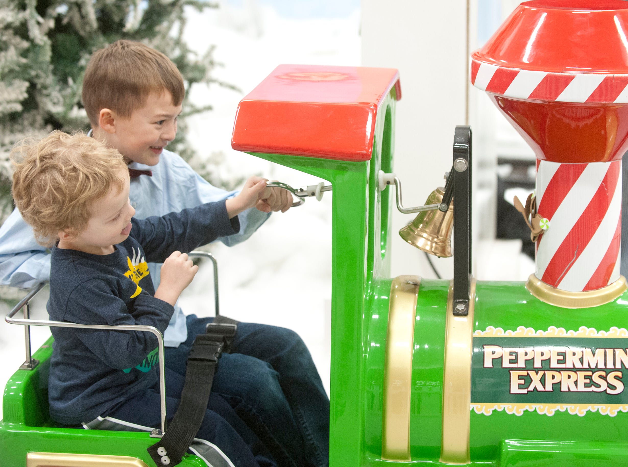 """Joshie Ferguson, age 4, left, and his cousin, Abram Williford, age 6, of Jeffersontown, right, ring the bell on the Peppermint Express train ride at the Galt House Hotel's  """"Breakfast with Santa.""""22 December 2018"""