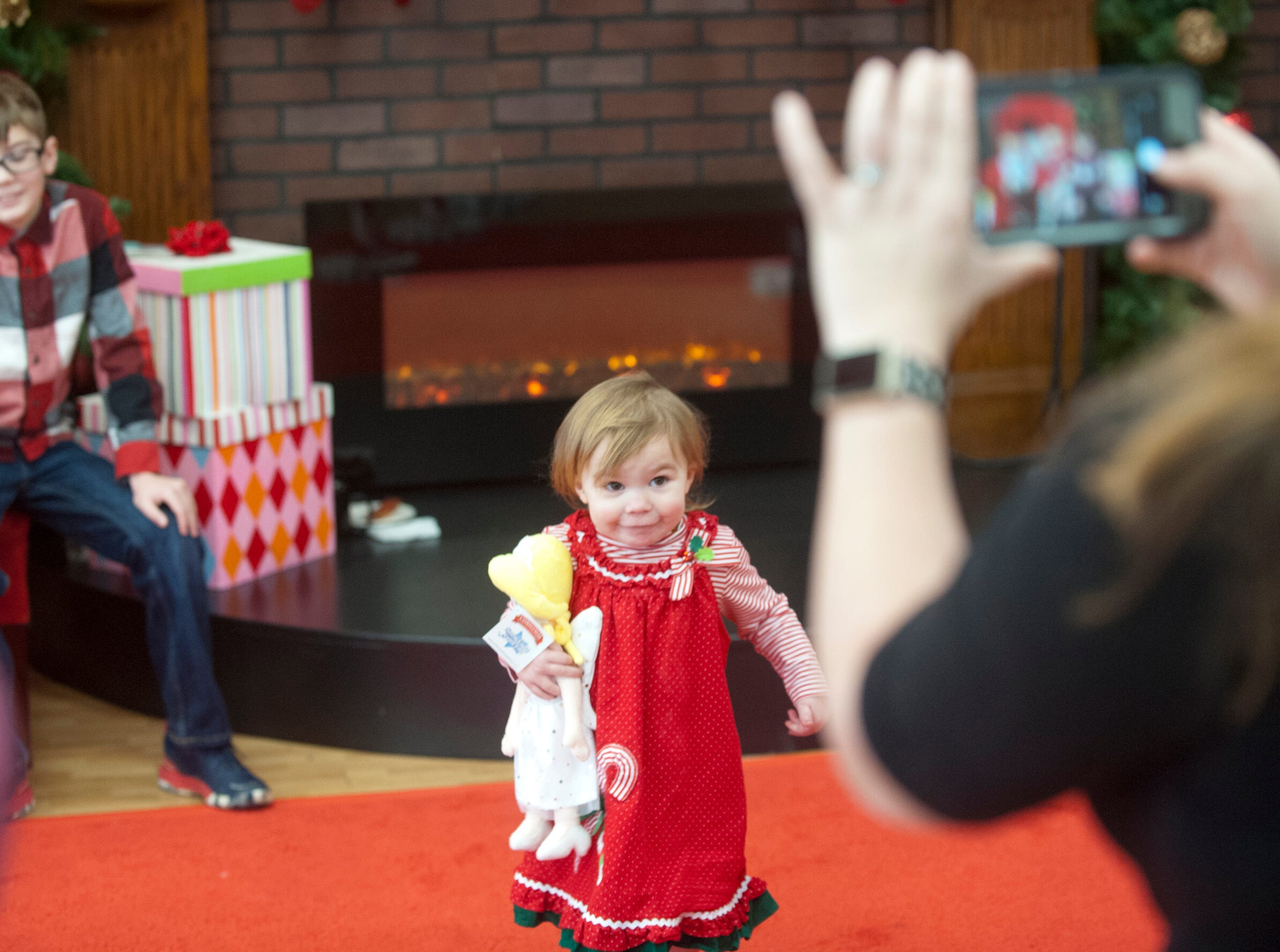 """A shy Olivia Rogers, age 2, of Versailles, Ky., wouldn't sit with Santa for a portrait, so mom snaps her and her new doll in front of a fireplace to the right ofSanta and his chair at the Galt House Hotel's """"Breakfast with Santa"""" event.22 December 2018"""