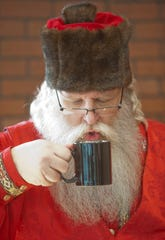"""Santa Claus (Murray McCandless) blows on a hot drink during his break at the Galt House Hotel's event,  """"Breakfast with Santa.""""22 December 2018"""