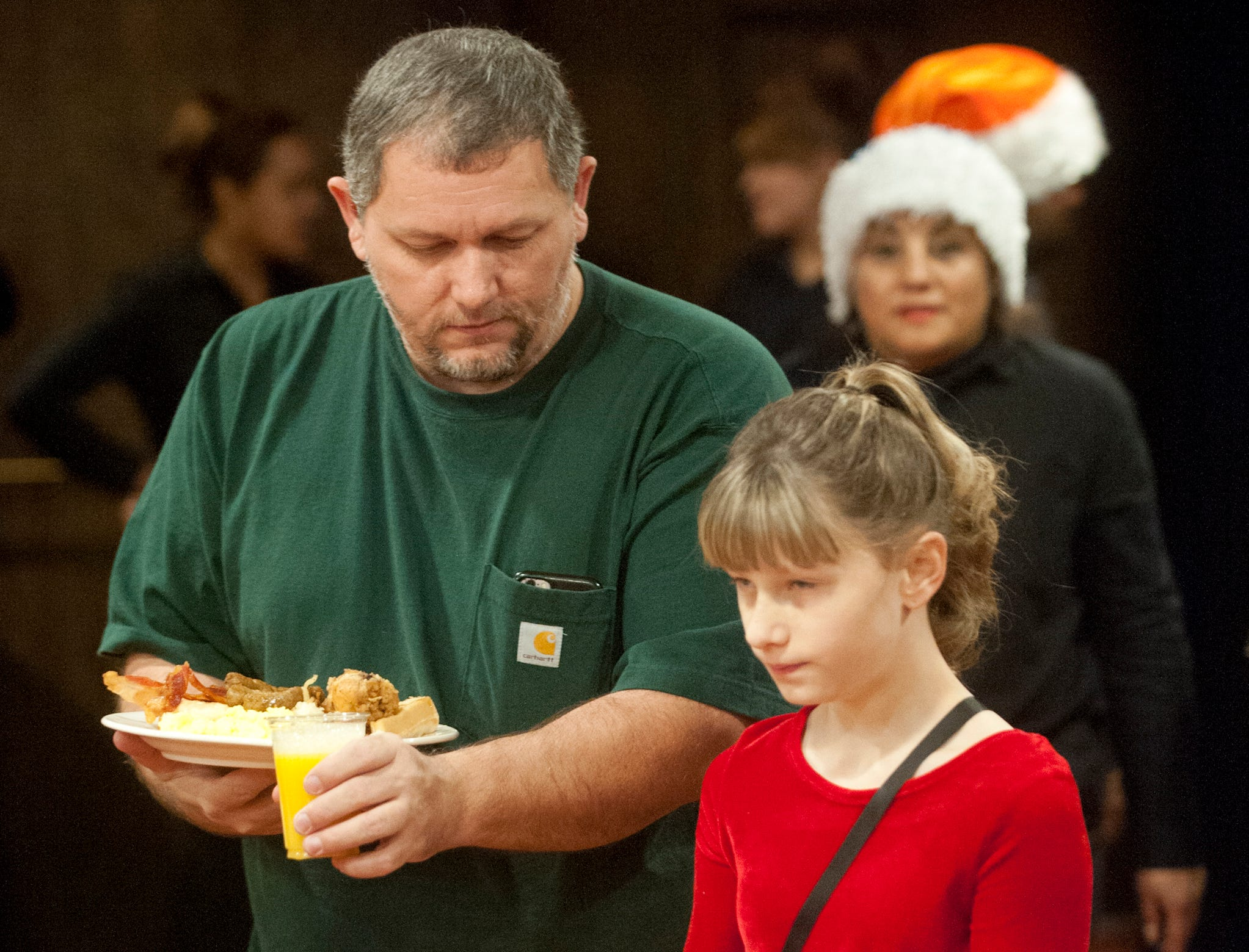 """Rocky Blair of Hodgenville, Ky., and his daughter, Lilly, take their plates of food to the table at the Galt House Hotel's   """"Breakfast with Santa"""" event.22 December 2018"""