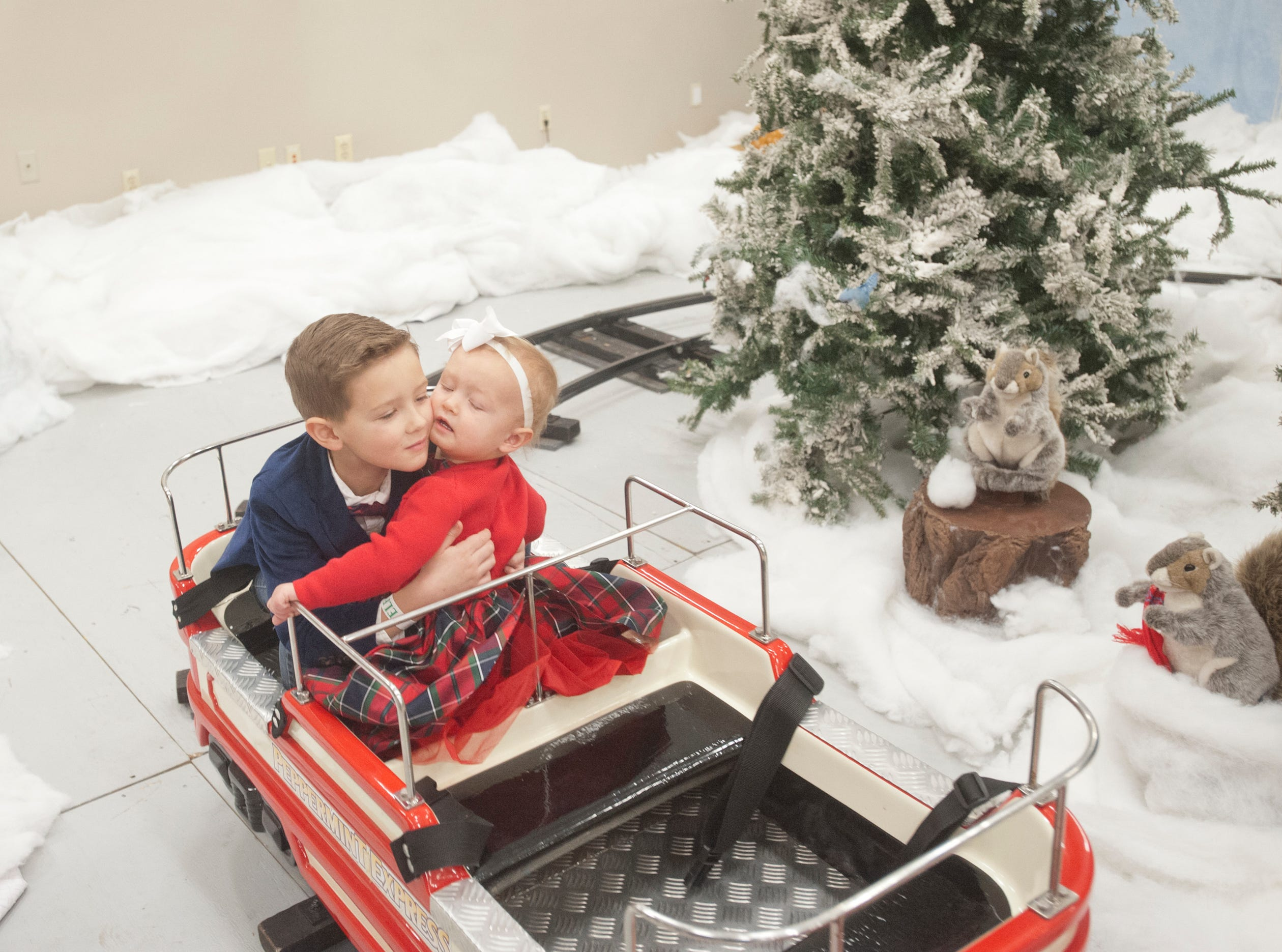 """Preston Pitts, age 6, holds on tight to hi sister, Evelyn, age 2, as they occupy the last car of the Peppermint Express train ride at the Galt House Hotel's """"Breakfast with Santa"""" event.22 December 2018"""