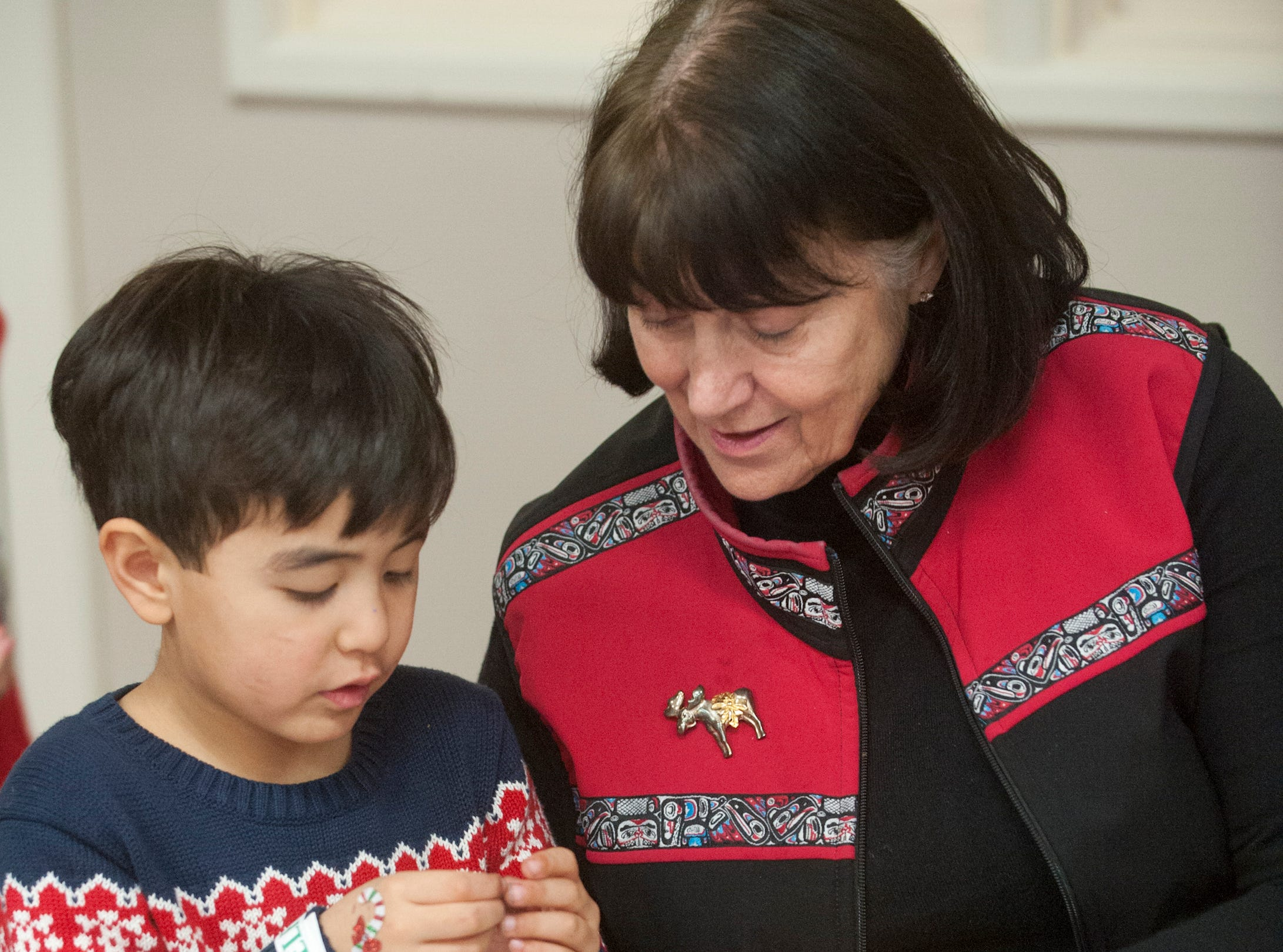 """John Yu, age 5, of New York City crafts a gingerbread man with the help of his grandmother, Darlene Horton  of Prospect, at the Galt House Hotel's sold-out event,  """"Breakfast with Santa.""""22 December 2018"""