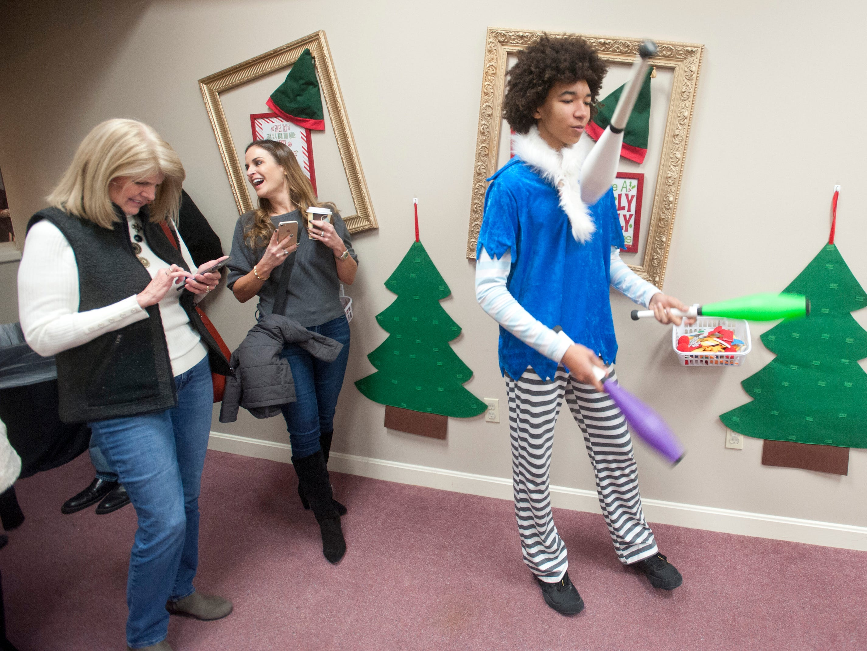 """Donna Hundley of Jeffersontown and Tonya Moore of Louisville's east end text to friends a juggler Michael Crinot of the highlands entertains them at the Galt House Hotel's sold-out event,  """"Breakfast with Santa.""""22 December 2018"""