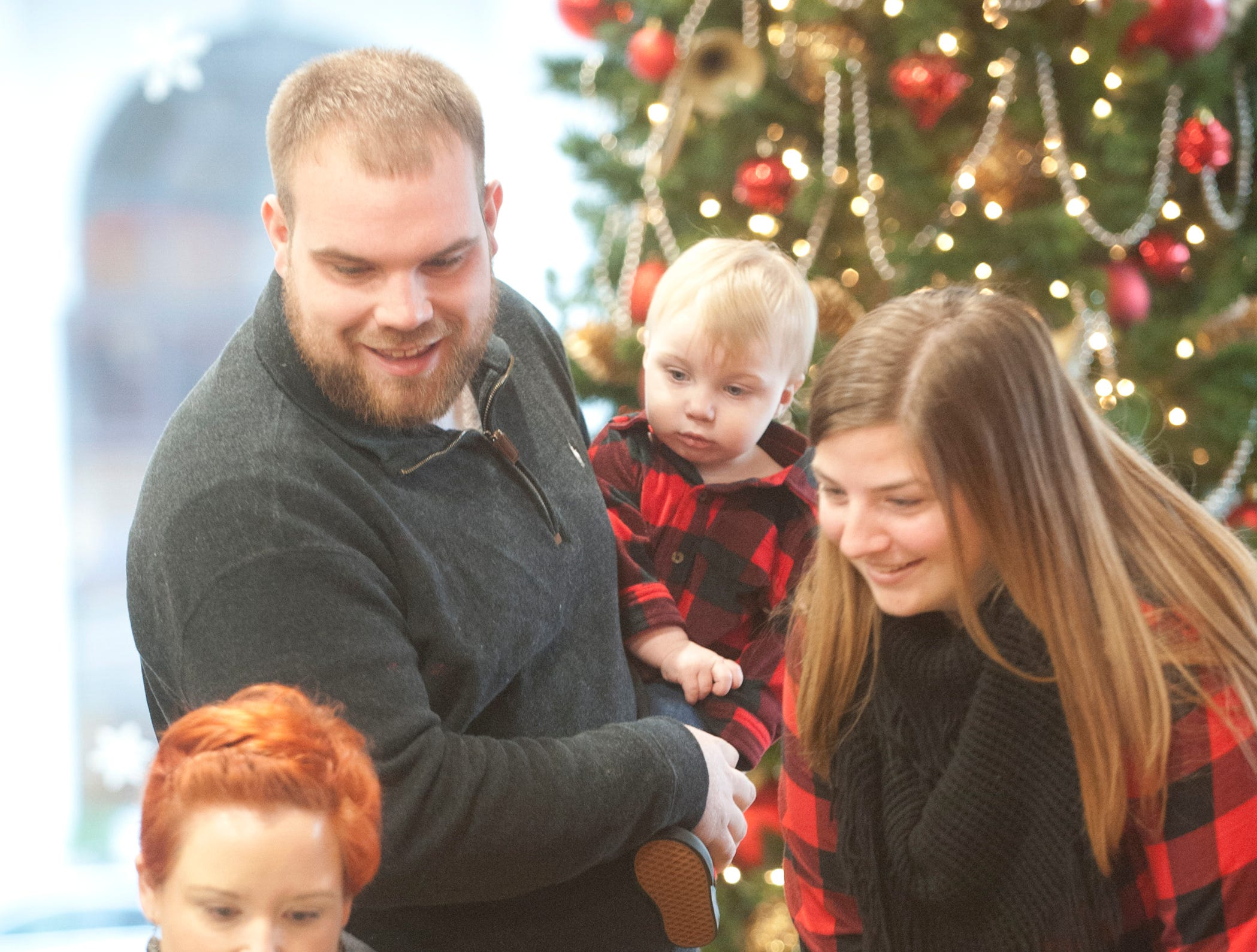 """Dalton and Cameron Estep of Pleasure Ridge Park and their son, Jaxon, 11 months check out the photo taken of Jaxon and Santa at the Galt House Hotel's """"Breakfast with Santa"""" event. Working the computer is Shanna Simpon with Melissa G's Photo Studio.22 December 2018"""