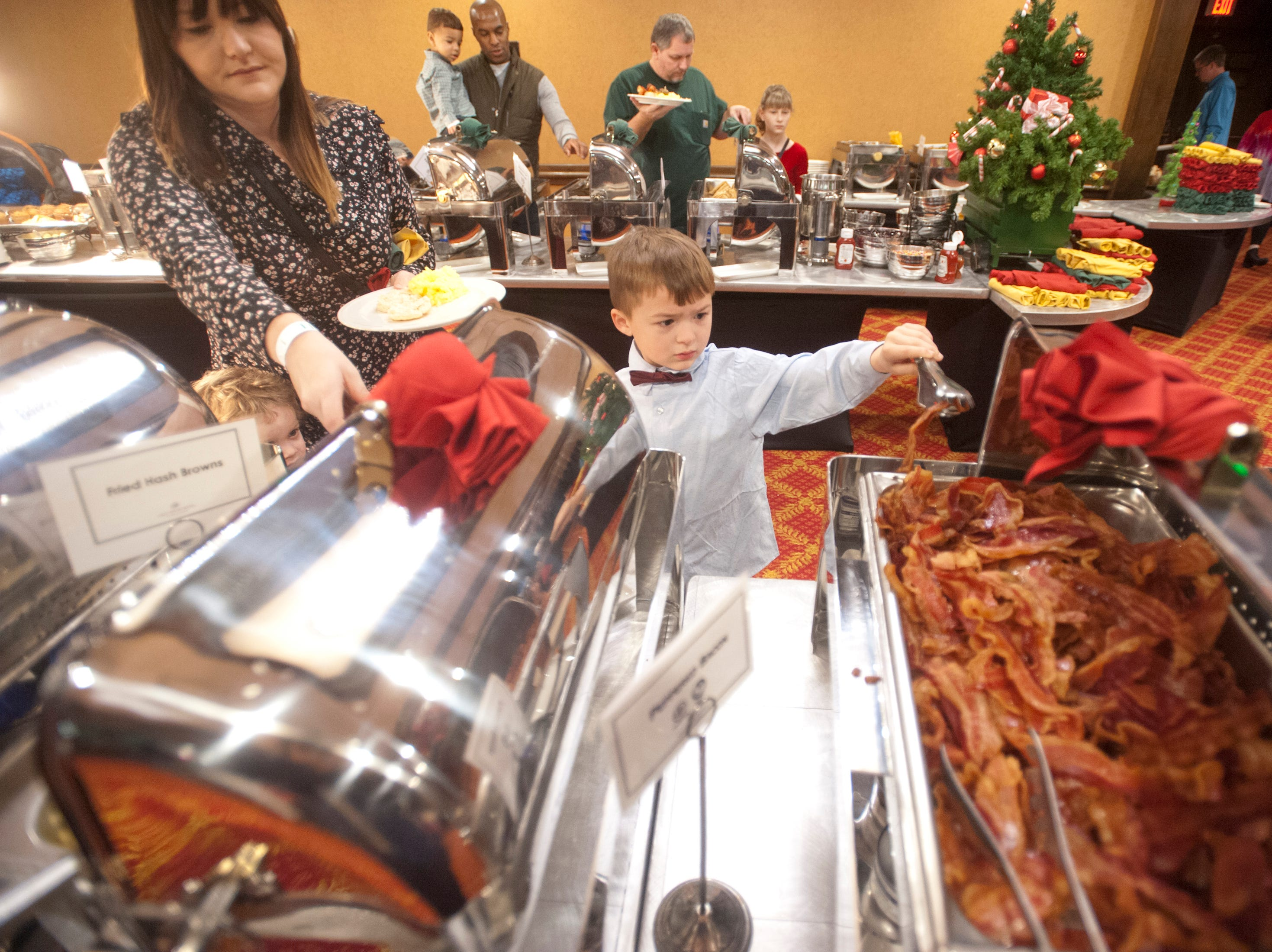 """Abram Ferguson, age 6, of Jeffersontown, tries to get some bacon on his plate at the Galt House Hotel's sold-out event,  """"Breakfast with Santa."""" His mother, Rebecca, is at left.22 December 2018"""
