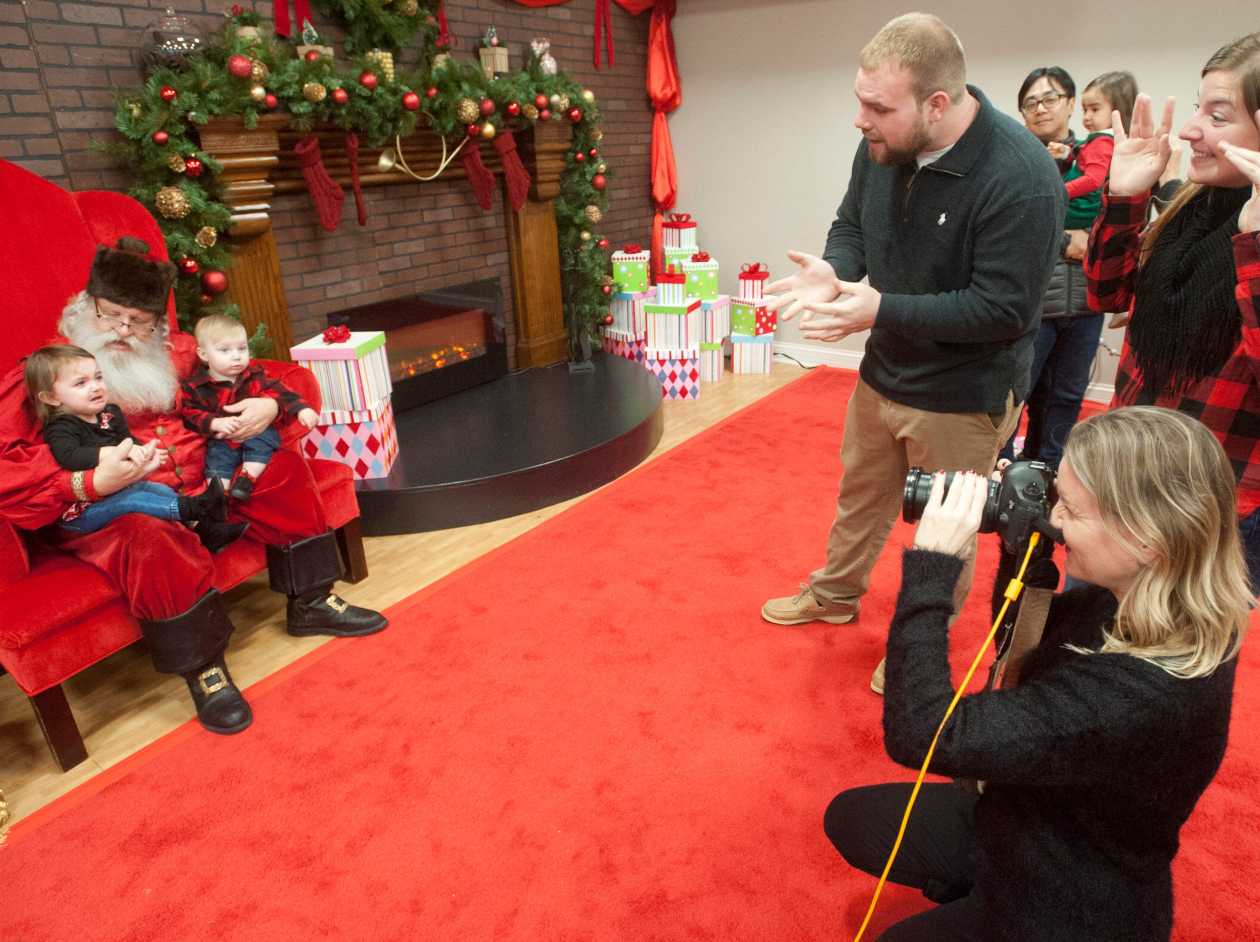 """Dalton and Cameron Estep of Pleasure Ridge Park make fun faces at their niece, Harper, age one (left), and their son, Jaxon, 11 months while the two youngsters have their photo made with Santa at the Galt House Hotel's sold-out event,  """"Breakfast with Santa."""" Taking the photo is Mellisa G. Schroeder of Meissa G's photo studio.22 December 2018"""