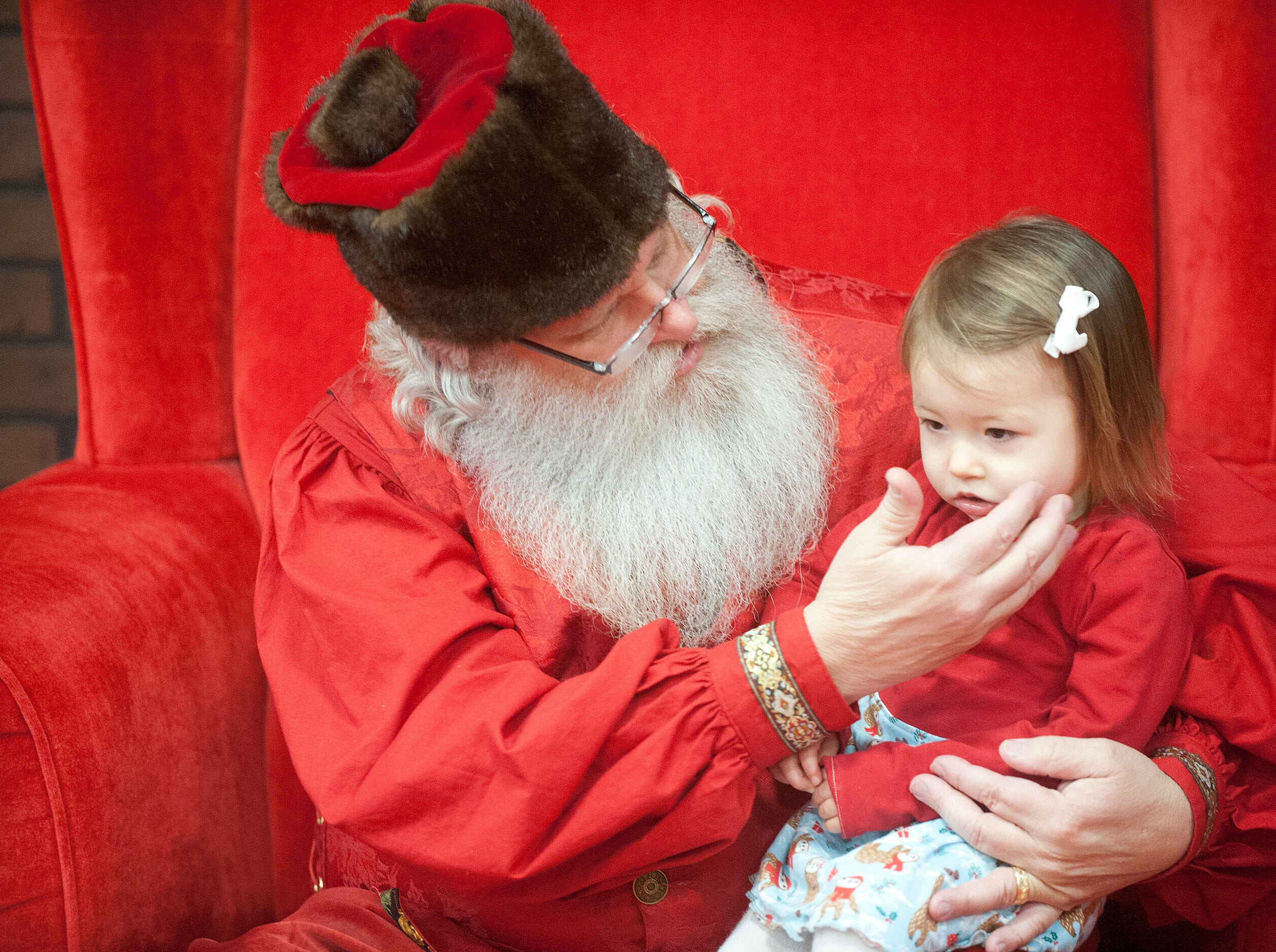 """Santa Claus (Murray McCandless) gently touches the cheek of a  very shy Delila Yurich, age 2, of Roanoke, Va. at the Galt House Hotel's sold-out event,  """"Breakfast with Santa."""" Yurich was in town to visit her grandparents who live in Louisville.22 December 2018"""