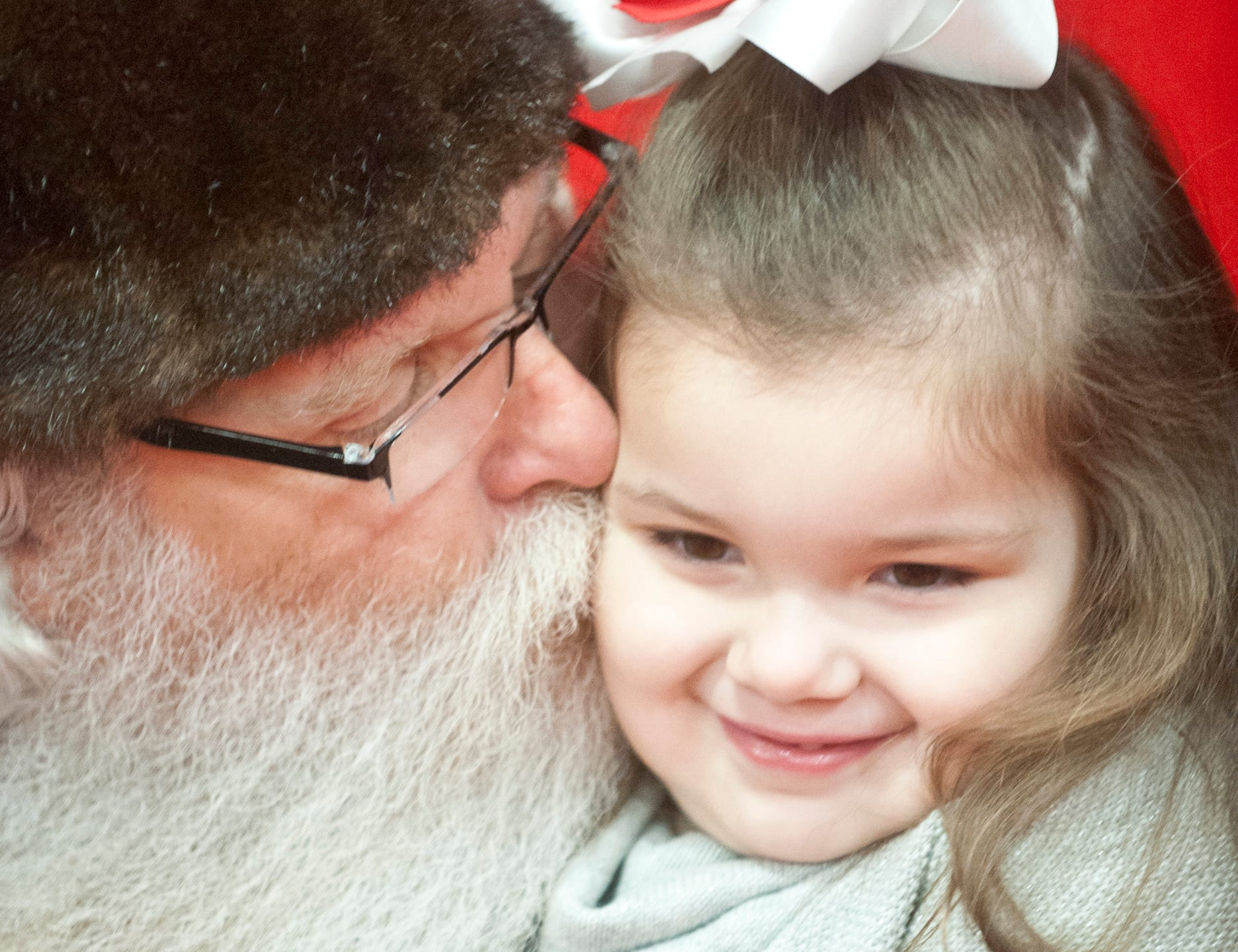 """Santa Claus (Murray McCandless) plants a kiss on the cheek of Khlo Knopp, age 4, of Springfield, Ky., at the Galt House Hotel's sold-out event, """"Breakfast with Santa."""" 22 December 2018"""