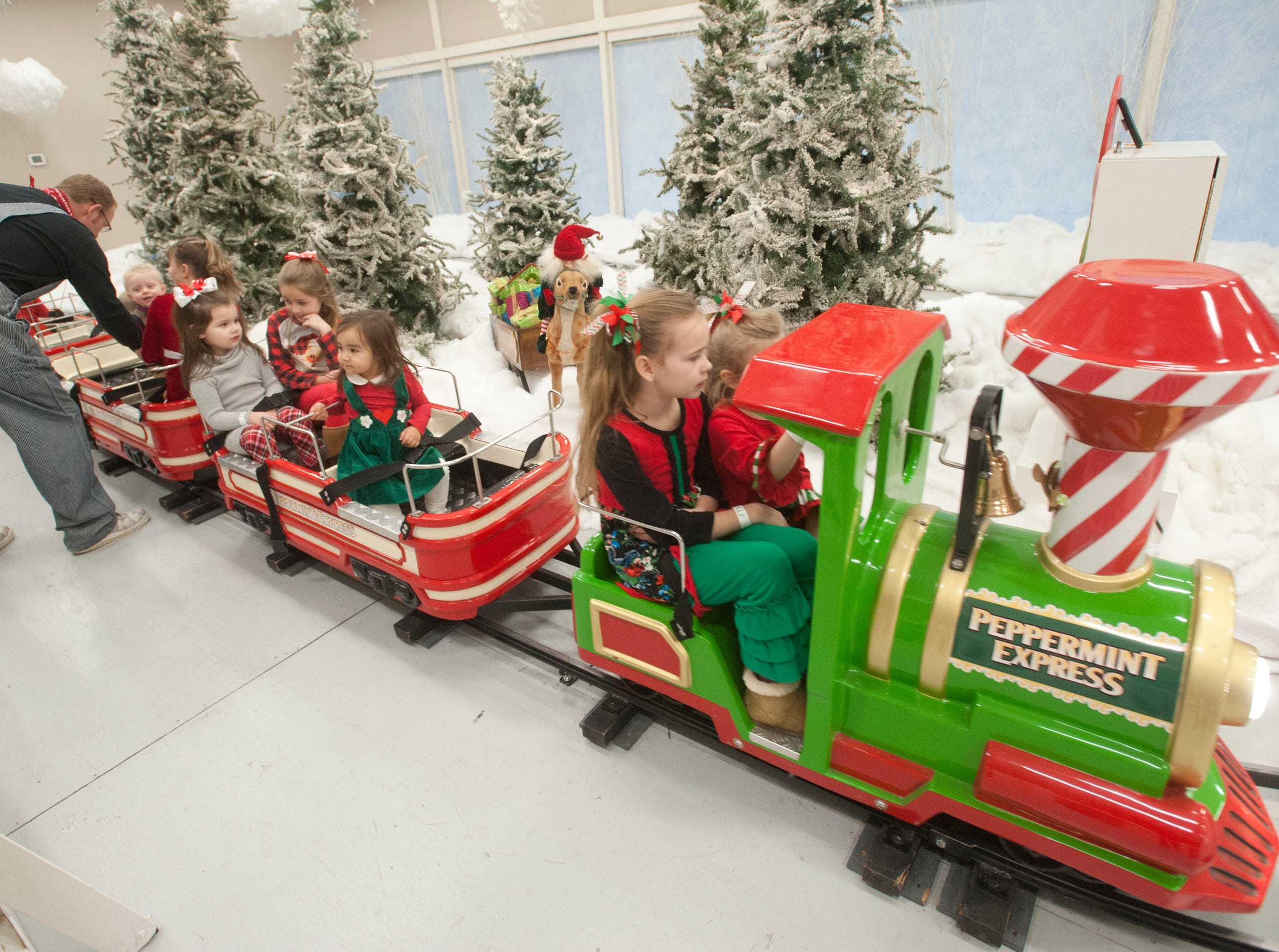 """A trainman helps passengers into Peppermint Express train cars at the Galt House Hotel's sold-out event,  """"Breakfast with Santa.""""22 December 2018"""