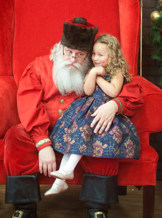 """Santa Claus (Murray McCandless) listens as Emily Marrs, age 3, of Indianapolis, tells him what she wants for Christmas. They were at the Galt House Hotel's """"Breakfast with Santa"""" event. 22 December 2018"""