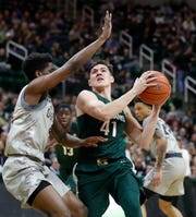 Michigan State guard Conner George (41) is defended by Oakland guard Stan Scott during the second half of an NCAA college basketball game in 2018, in East Lansing.