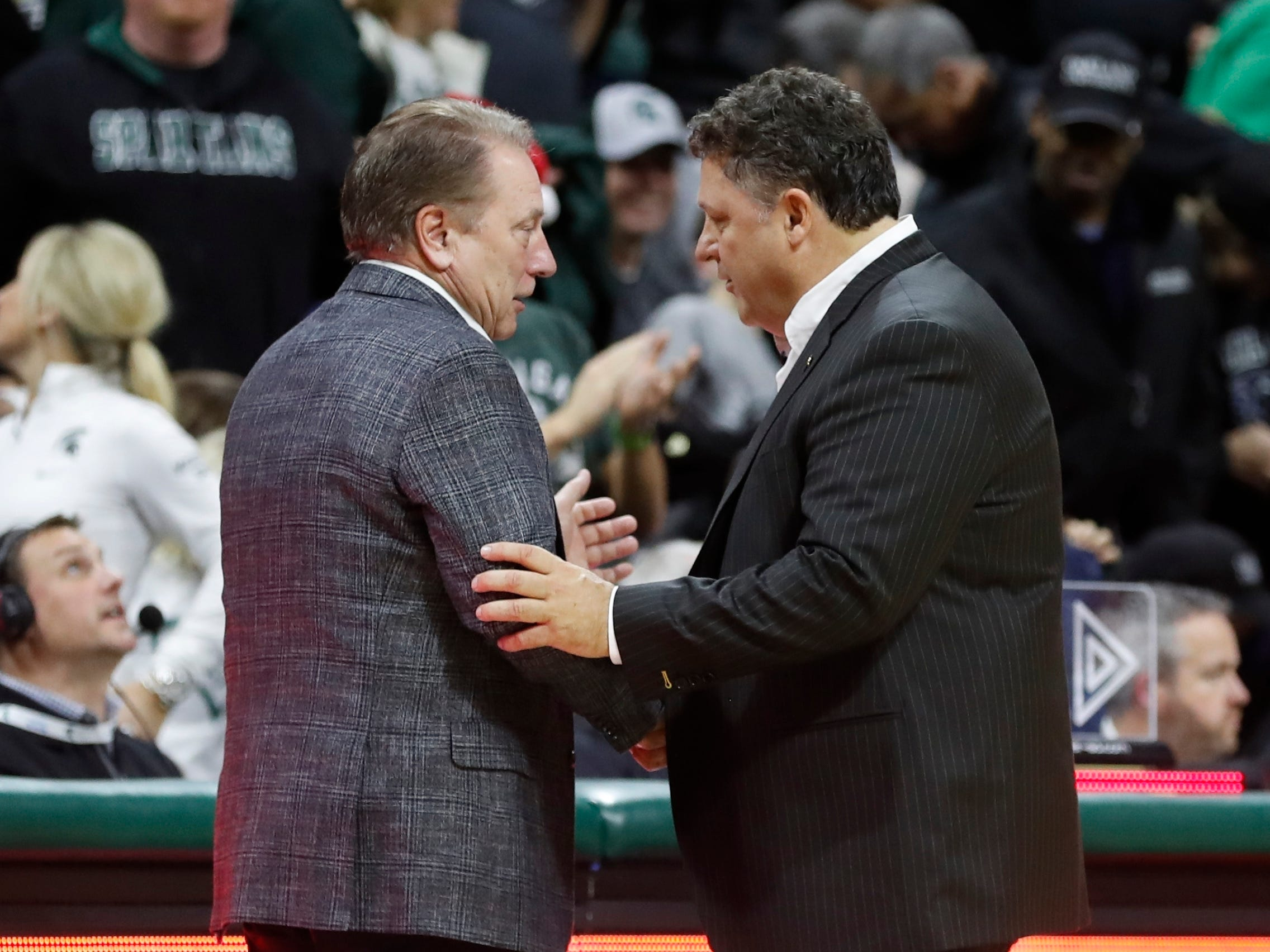 Michigan State head coach Tom Izzo, left, meets with Oakland head coach Greg Kampe after an NCAA college basketball game, Friday, Dec. 21, 2018, in East Lansing, Mich.