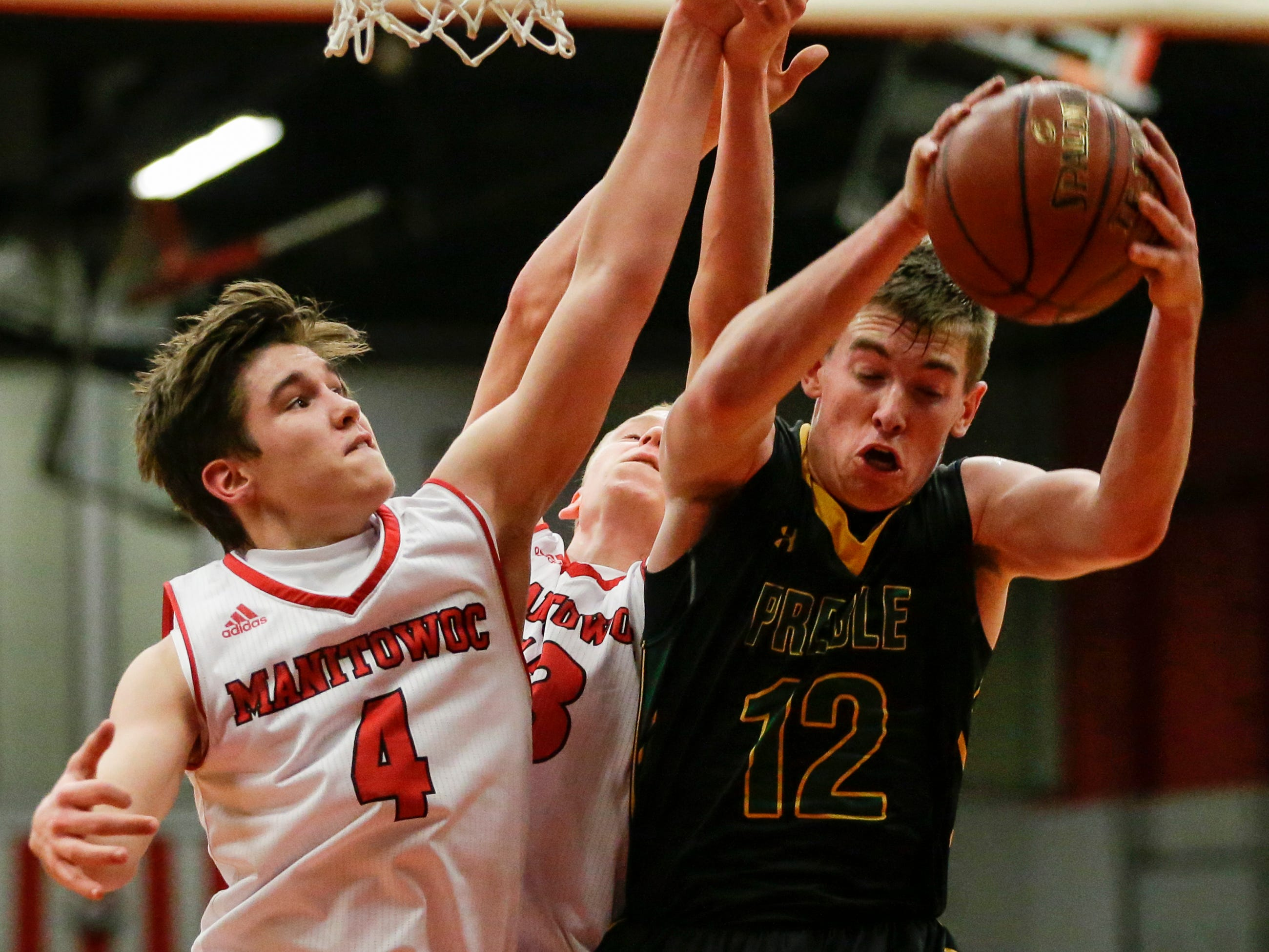 Green Bay Preble's Josh Nicklaus gets the rebound against Manitowoc Lincoln's Mason Dopirak and Sam Jacobson (13) during boys FRCC basketball at Manitowoc Lincoln High School Friday, December 21, 2018, in Manitowoc, Wis. Joshua Clark/USA TODAY NETWORK-Wisconsin