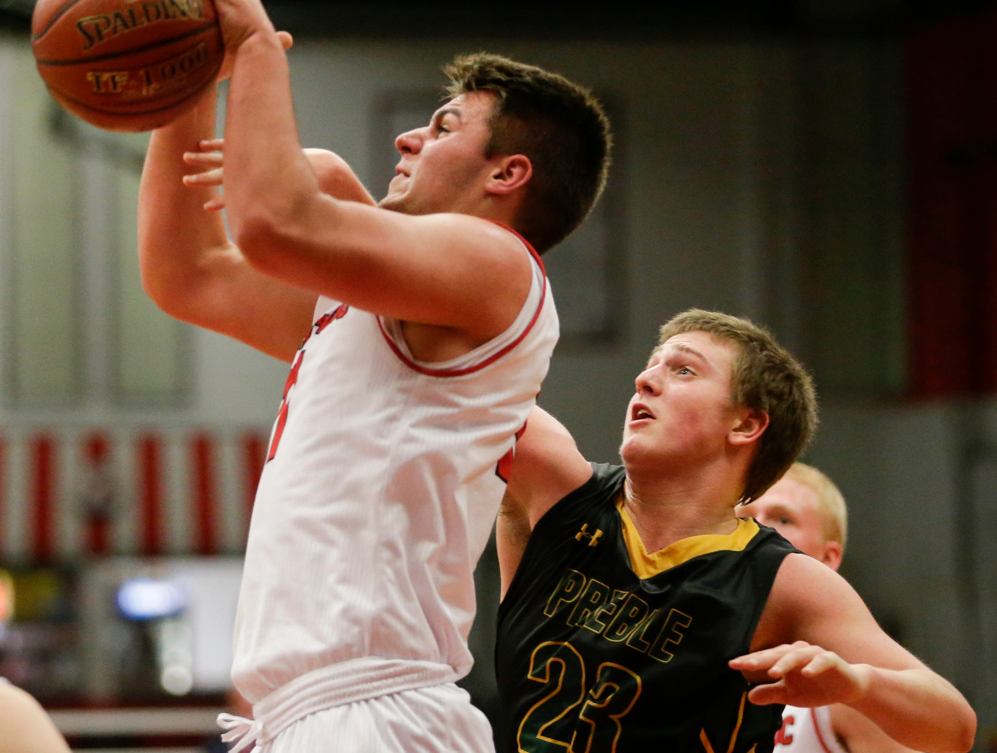 Manitowoc Lincoln's Davis Heinzen (11) gets a shot blocked from behind by Green Bay Preble's Bryan Boockmeier (23) during boys FRCC basketball at Manitowoc Lincoln High School Friday, December 21, 2018, in Manitowoc, Wis. Joshua Clark/USA TODAY NETWORK-Wisconsin