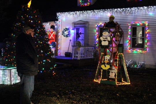 Steve Moneysmith stands in front of a lit up motorized ferris wheel he made five years ago. It is just one part of his annual Christmas display, one he says continues to grow.