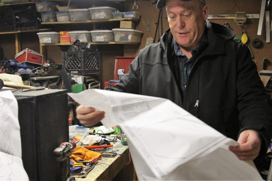 Steve Moneysmith looks over a set of blueprints for one of his front yard creations Wednesday evening. Always fascinated with woodwork, he has created 20 signs and other fixtures to be displayed at his house, 314 Whetstone River Road South, during the winter season.