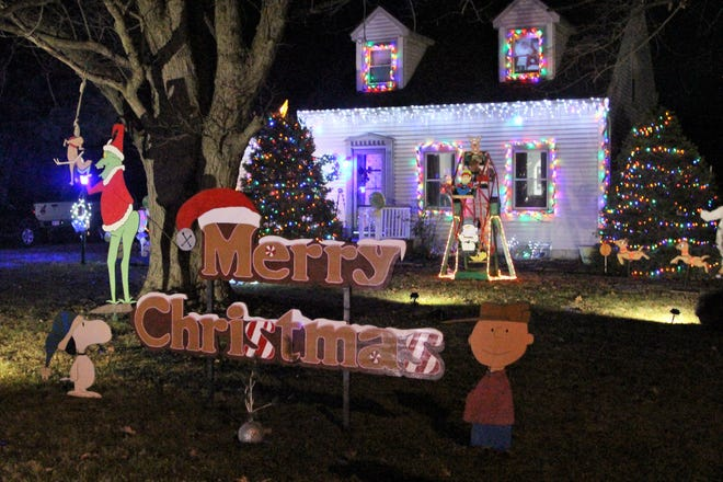 A homemade sign is flanked by Charlie Brown and Snoopy in front of Steve Moneysmith's home on Whetstone River Road South. He has been adding to the collection of Christmas decorations since moving into the neighborhood with his wife Deana almost 20 years ago.