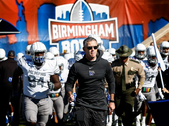 Memphis coach Mike Norvell leads his team onto the field for the Birmingham Bowl.