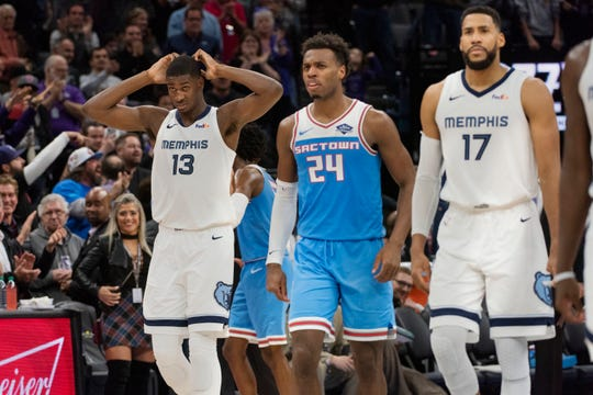 Memphis Grizzlies forward Jaren Jackson Jr. (13), Sacramento Kings guard Buddy Hield (24), and Grizzlies guard Garrett Temple (17) react during the final seconds of an NBA basketball game in Sacramento, Calif., Friday, Dec. 21, 2018. The Kings won 102-99. (AP Photo/Randall Benton)