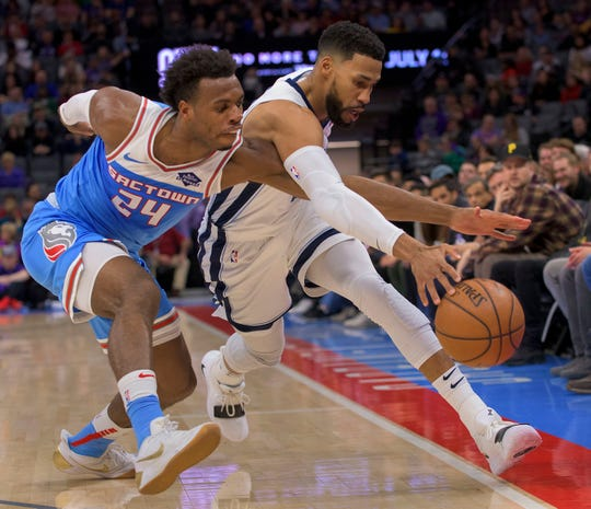 Sacramento Kings guard Buddy Hield (24) and Memphis Grizzlies guard Garrett Temple (17) chase the ball during the first quarter of an NBA basketball game in Sacramento, Calif. Friday, Dec. 21, 2018. (AP Photo/Randall Benton)