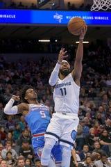 Memphis Grizzlies guard Mike Conley (11) lays the ball up past Sacramento Kings guard De'Aaron Fox (5) during the first quarter of an NBA basketball game in Sacramento, Calif. Friday, Dec. 21, 2018. (AP Photo/Randall Benton)