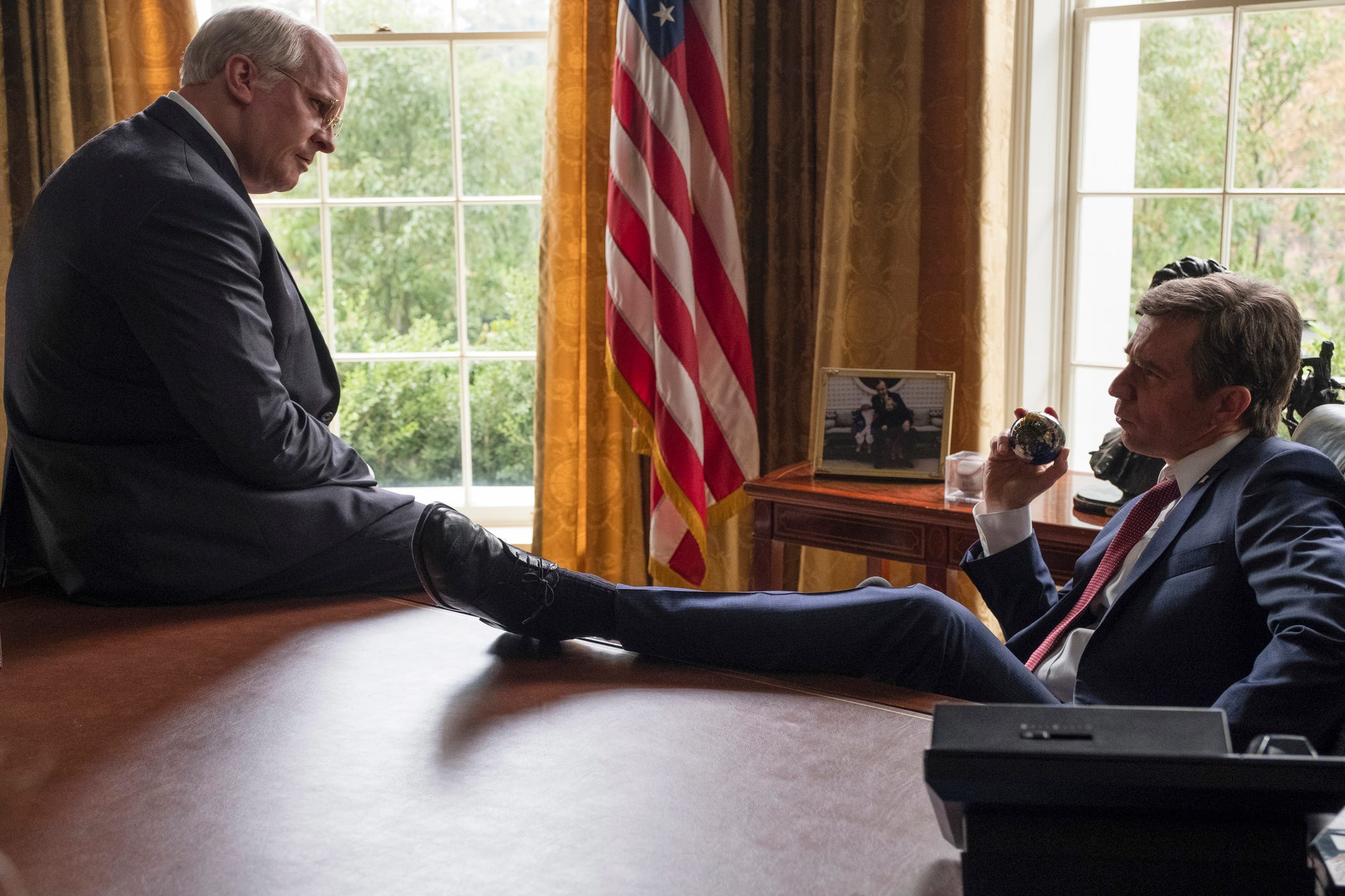 "Christian Bale (left, as Dick Cheney) and Sam Rockwell (as George W. Bush) in ""Vice."""