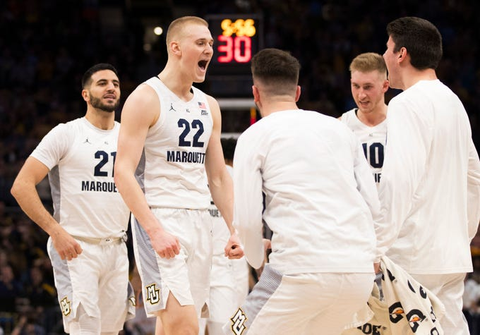 Golden Eagles forward Joey Hauser (22) is pumped up as he greets teammates during a timeout after he canned three straight three-pointers against Buffalo in the first half on Friday night at Fiserv Forum.