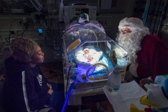 Greg Phelps (right) visits with Kenisha King and her baby, Jouri Williams, on Friday at St. Joseph's Hospital in Milwaukee. Phelps is in his 17th year playing Santa in St. Joe's neonatal intensive care unit. He was inspired by the Santa who visited his son, Kyle, when he was born prematurely at St. Joe's in 1998.