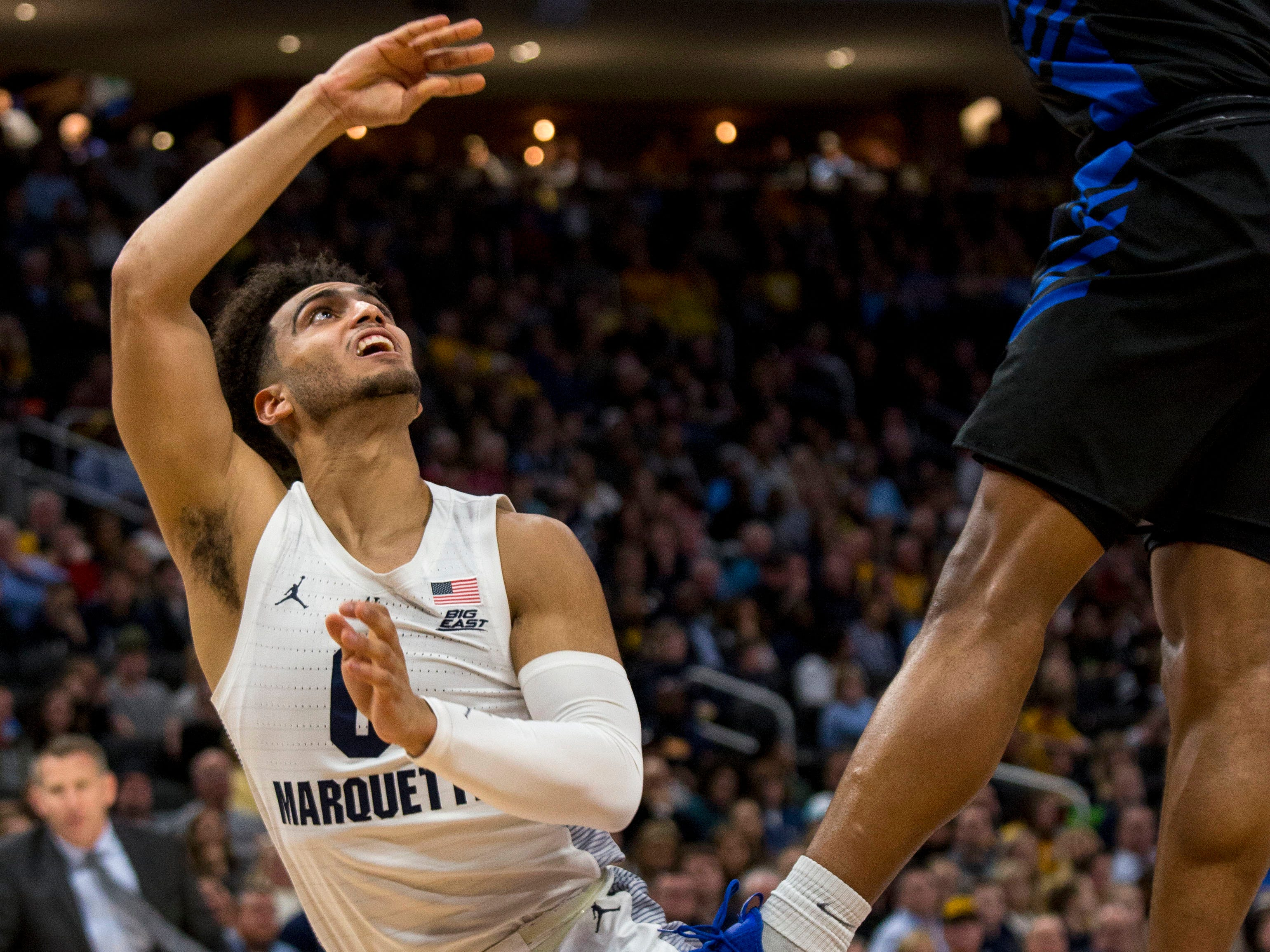 Buffalo guard Davonta Jordan blocks the shot attempt of Marquette guard Markus Howard, who had a tough first half in which he made just 1 of 7 shots on Friday night.