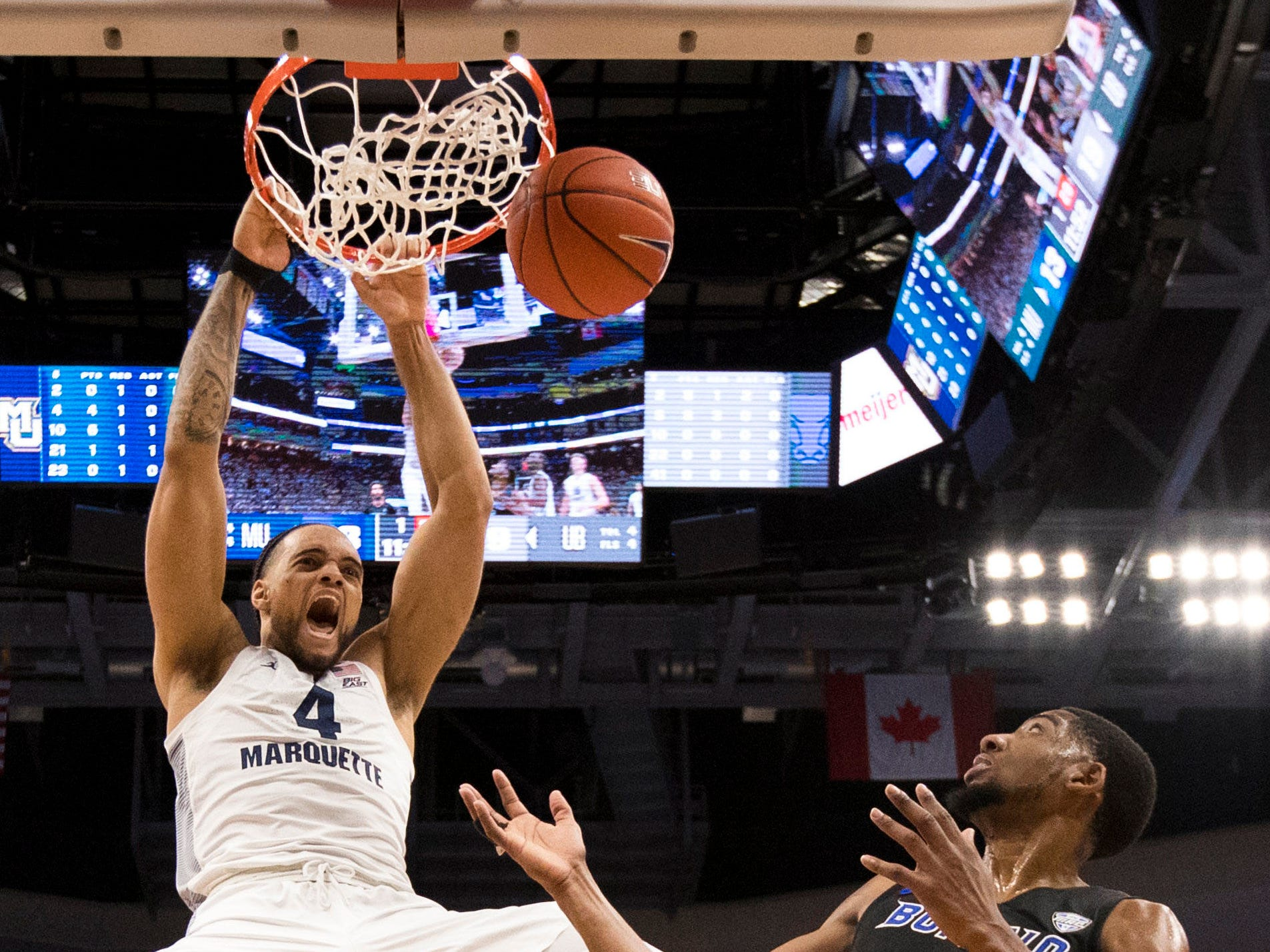 Marquette forward Theo John throws down an emphatic dunk against Buffalo during the first half Friday night.