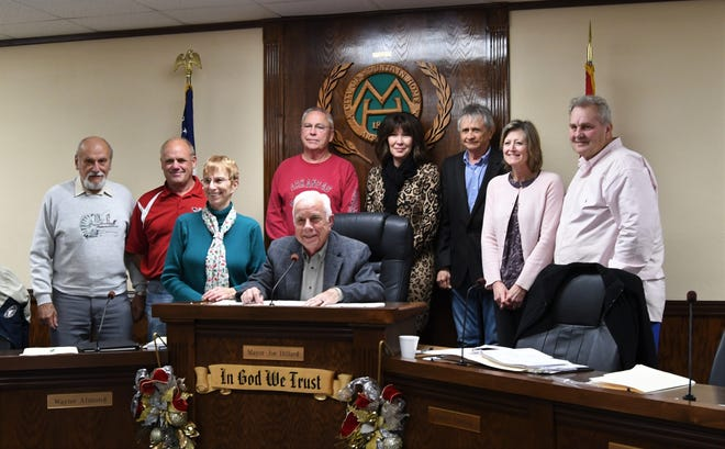 Members of the Mountain Home City Council gather around Mayor Joe Dillard (seated) for a final group photograph Thursday night. Dillard and four council members will be leaving office on Dec. 31.