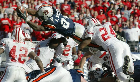 Auburn running back Carnell Williams (24) dives over for a touchdown as Wisconsin's LaMarr Watkins (24) and Robert Brooks (42) attempt to tackle in the Music City Bowl, Wednesday, Dec. 31, 2003, in Nashville, Tenn.  Auburn defeated Wisconsin 28-14.